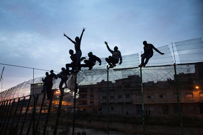 Sub-Saharan migrants climb over a metallic fence that divides Morocco and the Spanish enclave of Melilla, March 28, 2014.