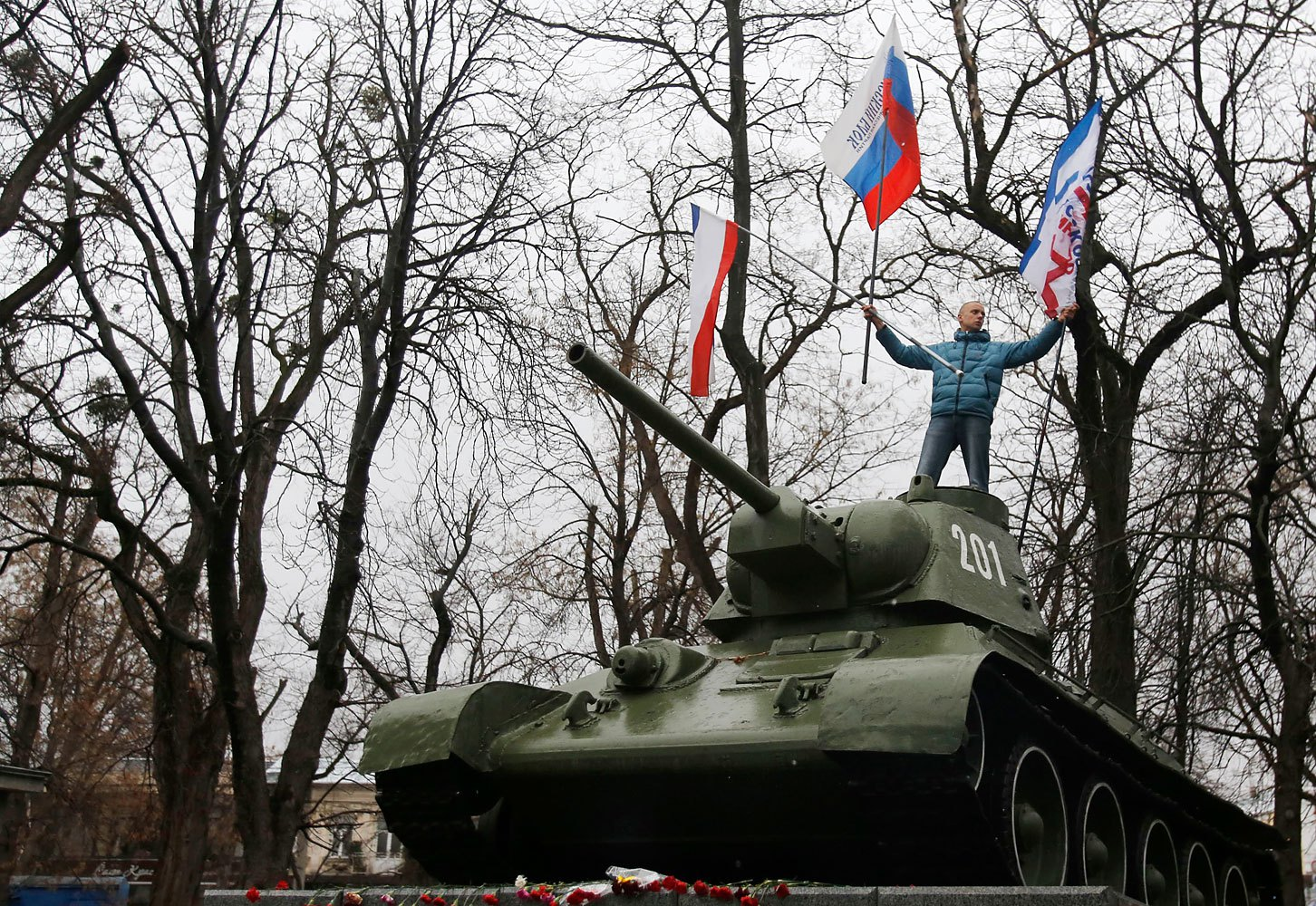 A Pro-Russian demonstrator waves Russian and Crimea flags atop an old Soviet Army tank during a protest in front of a local government building in Simferopol, Feb. 27, 2014.
