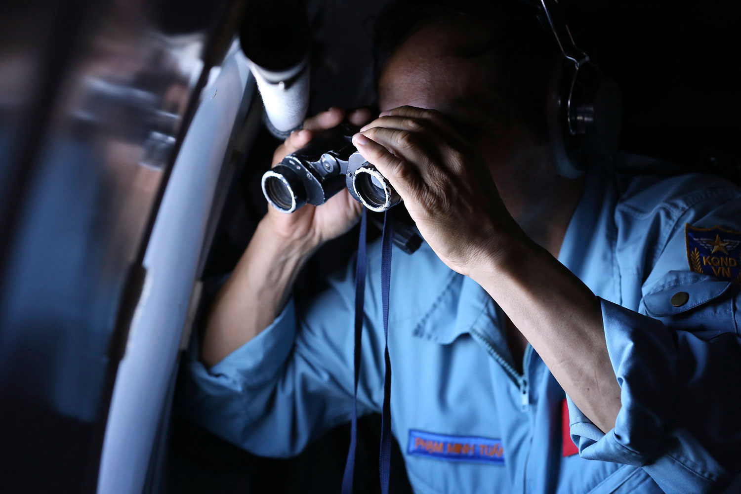 Vietnamese Air Force Col. Pham Minh Tuan uses binoculars on board an aircraft during a mission to search for the missing Malaysia Airlines Flight 370 in the Gulf of Thailand, on March 13, 2014.