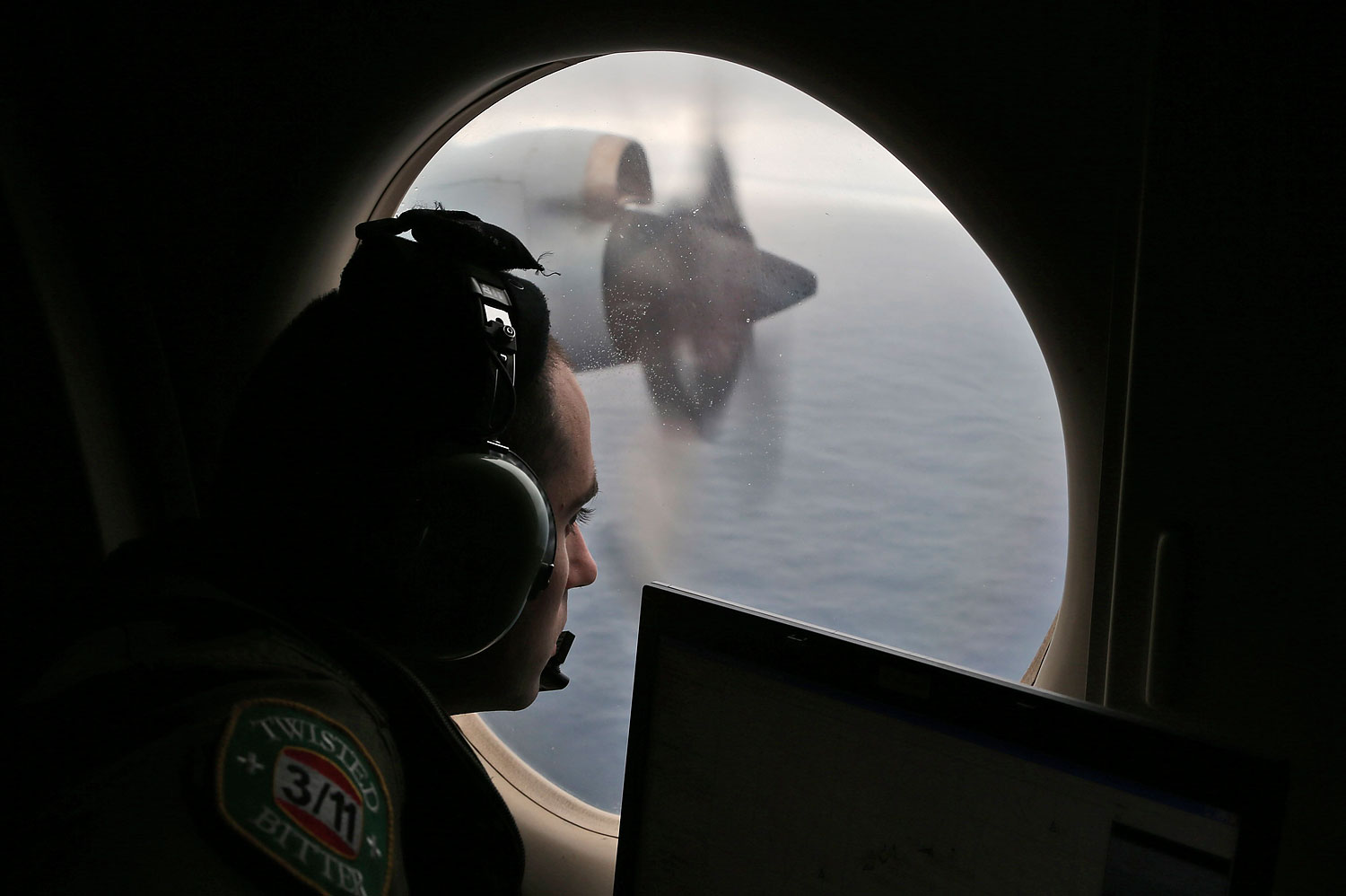 Flight officer Rayan Gharazeddine on board a Royal Australian Air Force AP-3C Orion, scans for the missing Malaysia Airlines Flight MH370 in southern Indian Ocean, Australia, March 22, 2014.
