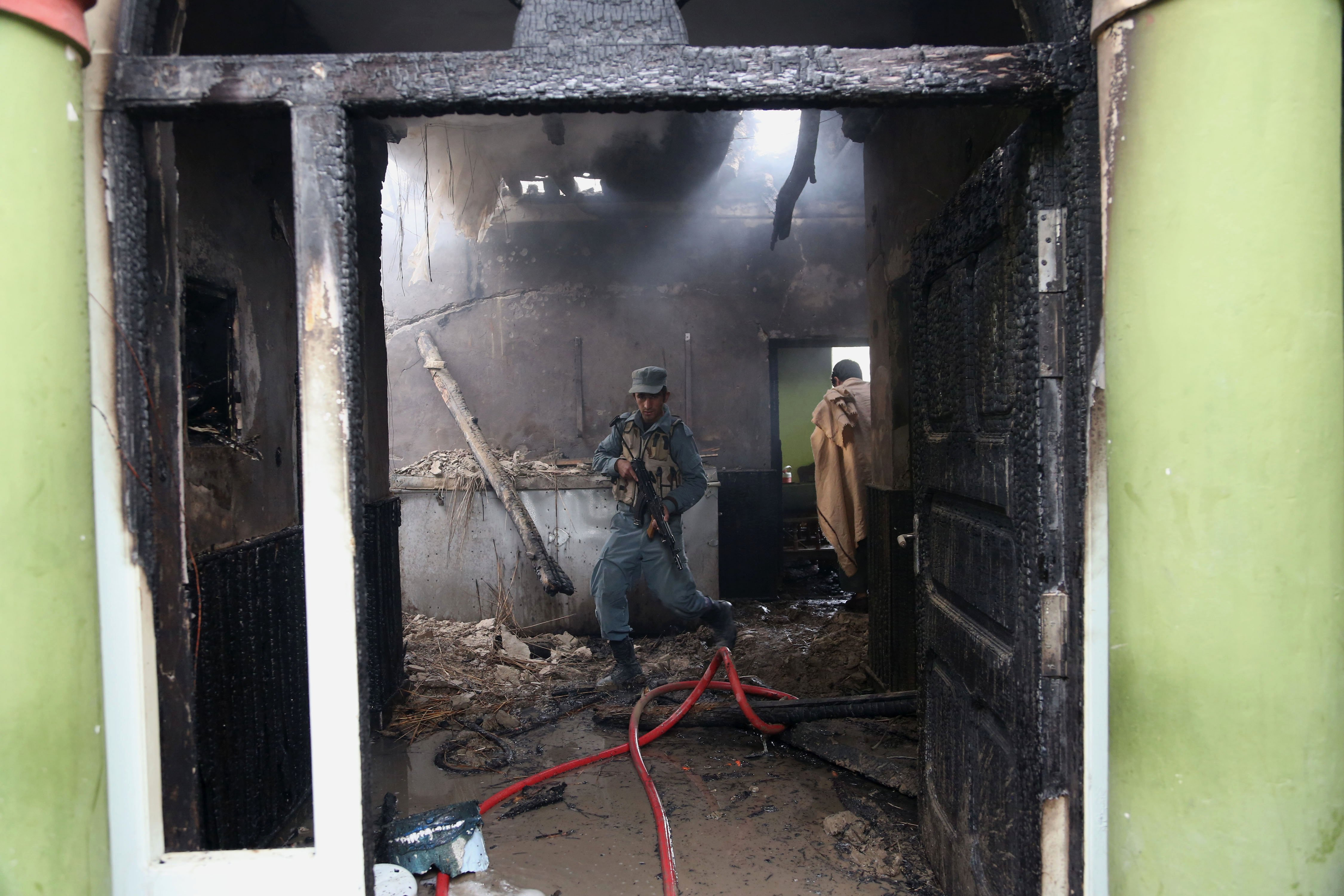 Mar. 20, 2014. An Afghan police officer walks around inside the nearby state-run Afghan radio and television building badly damaged when a suicide car bomber blew up his vehicle near a police station in Jalalabad, Afghanistan.