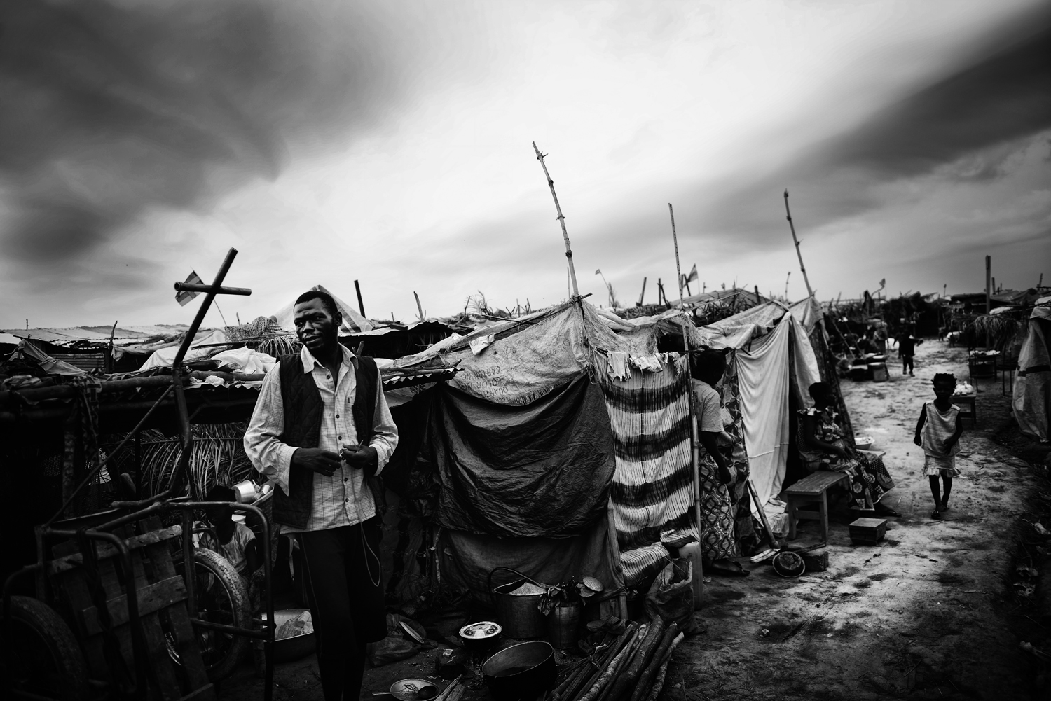 A man stands outside his tent in the refugee camp adjacent to Bangui M'Poko International Airport, which held some 120,000 people at its peak. Feb. 7, 2014.