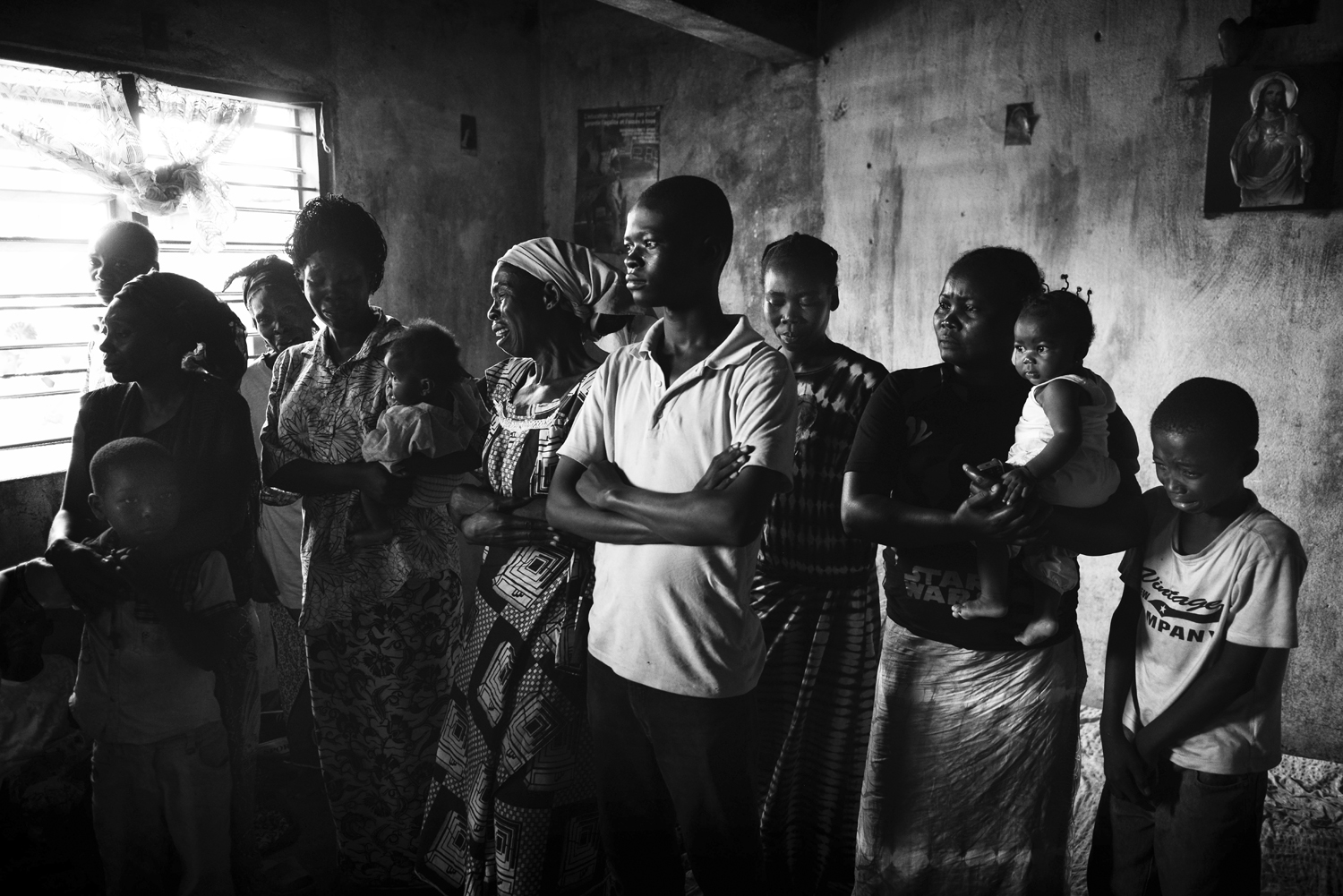 Members of a minister's family cry after he and a son were killed by militiamen, one day after the politician spoke out on the radio against the violence. Feb. 9, 2014.