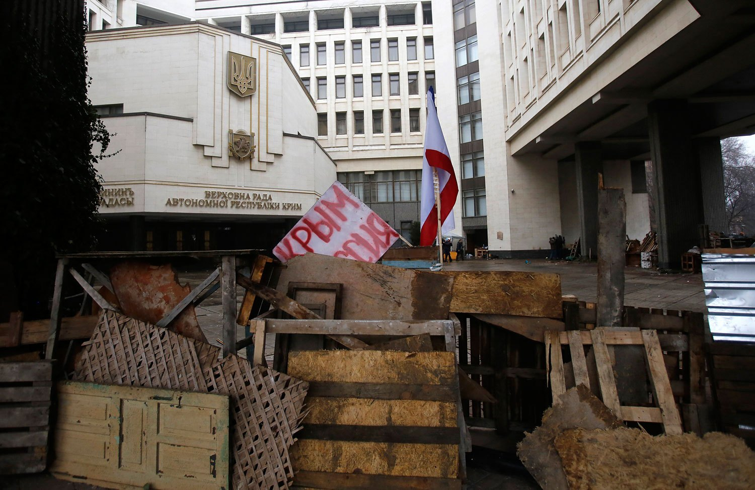 """Barricades block the entrance to government buildings in Simferopol, Crimea, with a banner that reads """"Crimea Russia,"""" Feb. 27, 2014."""