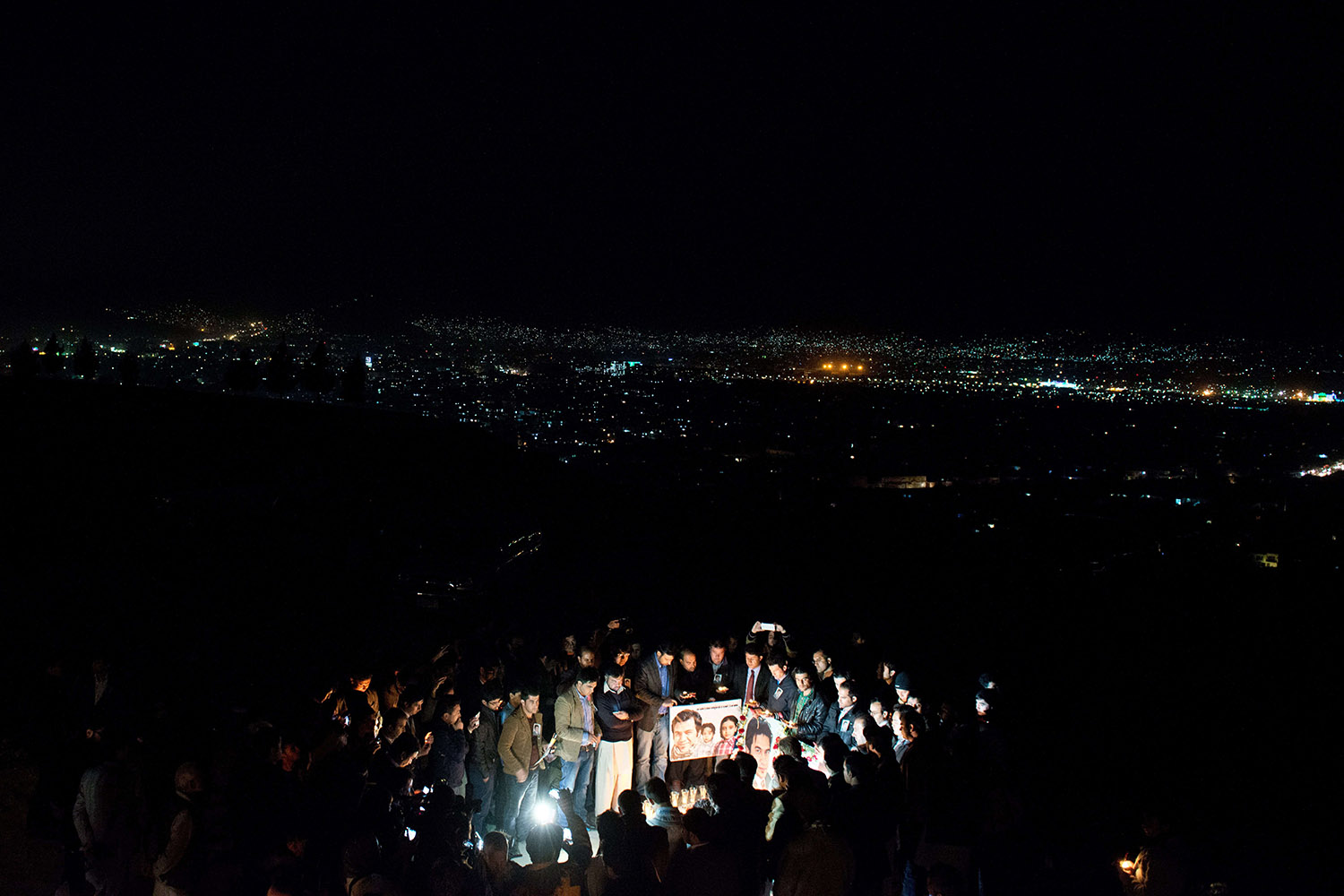 Mar. 26, 2014.                                Friends, family and colleagues of slain Afghan AFP reporter Sardar Ahmad gather as they take part in a candle light vigil in his honour, on a hill overlooking Kabul , Afghanistan.