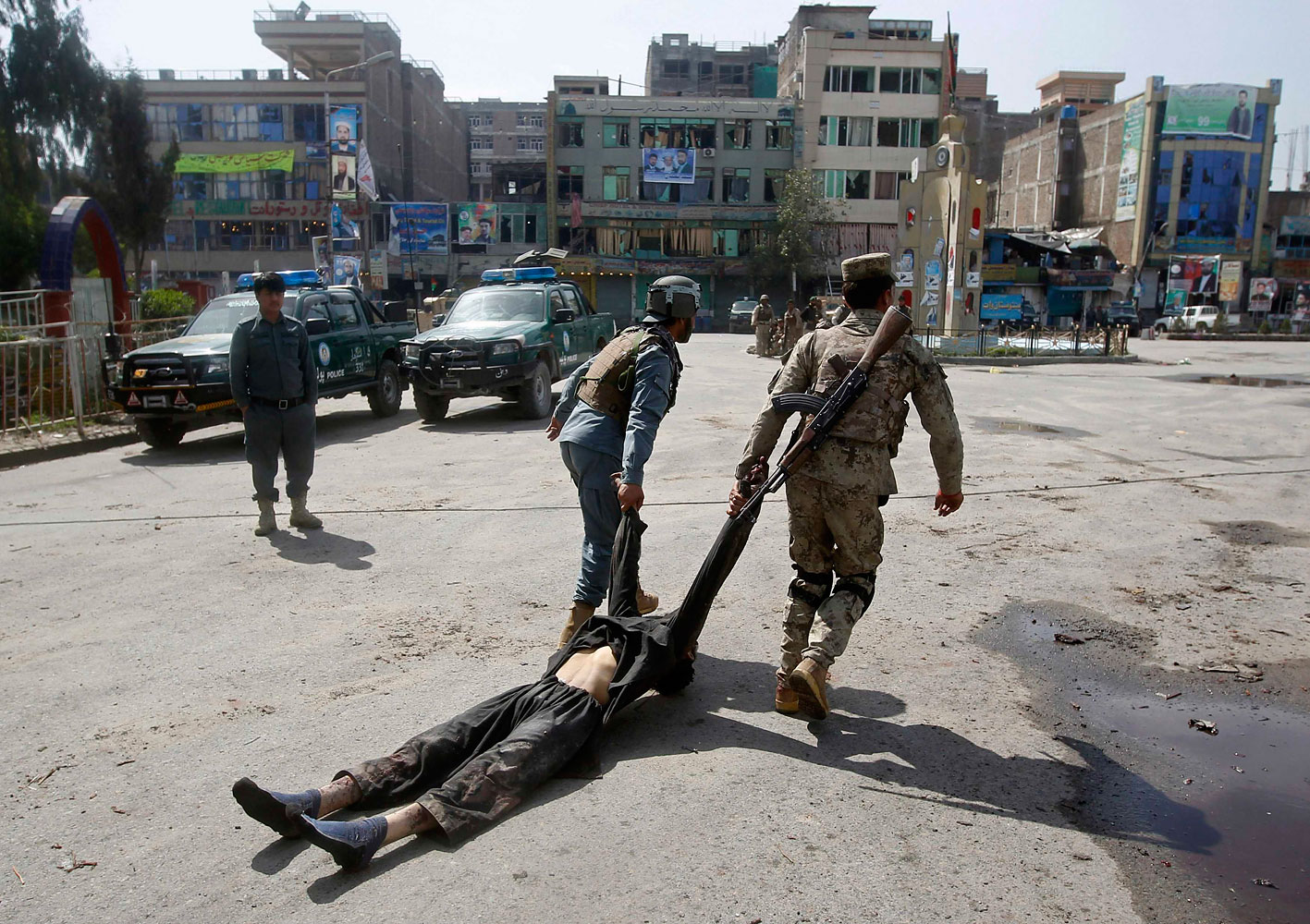 Afghan policemen remove the dead body of a Taliban insurgent from the site of a suicide car bomb attack in Jalalabad province, March 20, 2014.