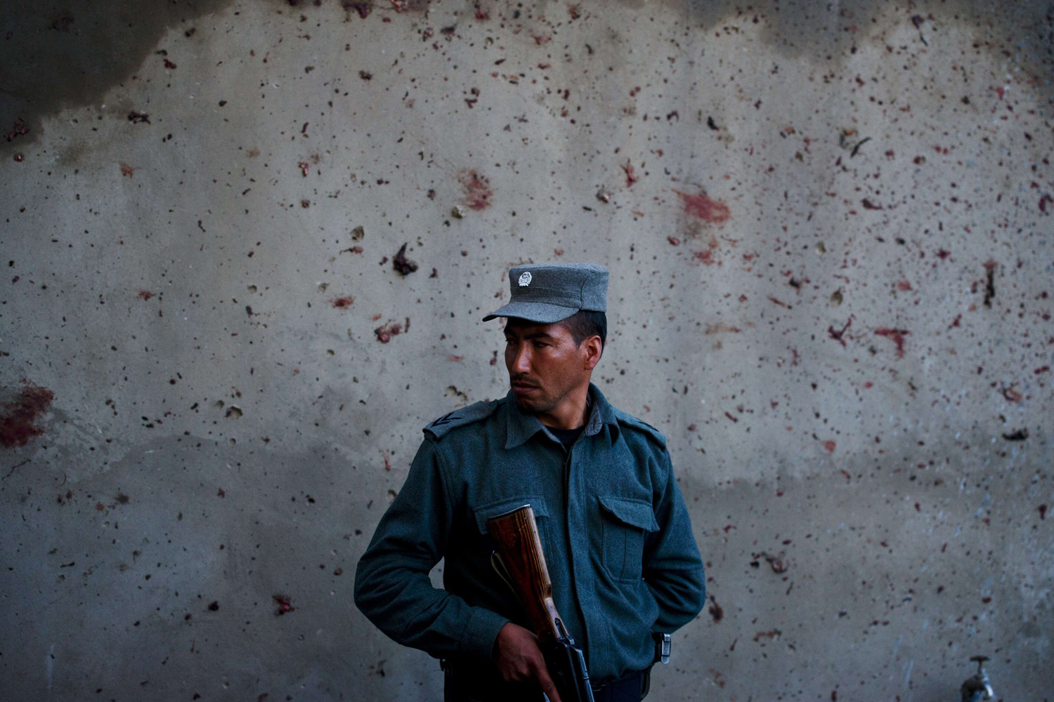 Mar. 25, 2014. An Afghan policeman stands in front of a wall stained by blood spatter at the site of an attack on an election commission office in Kabul. Fifteen people died in violence around Afghanistan less than a fortnight before the country's presidential poll.