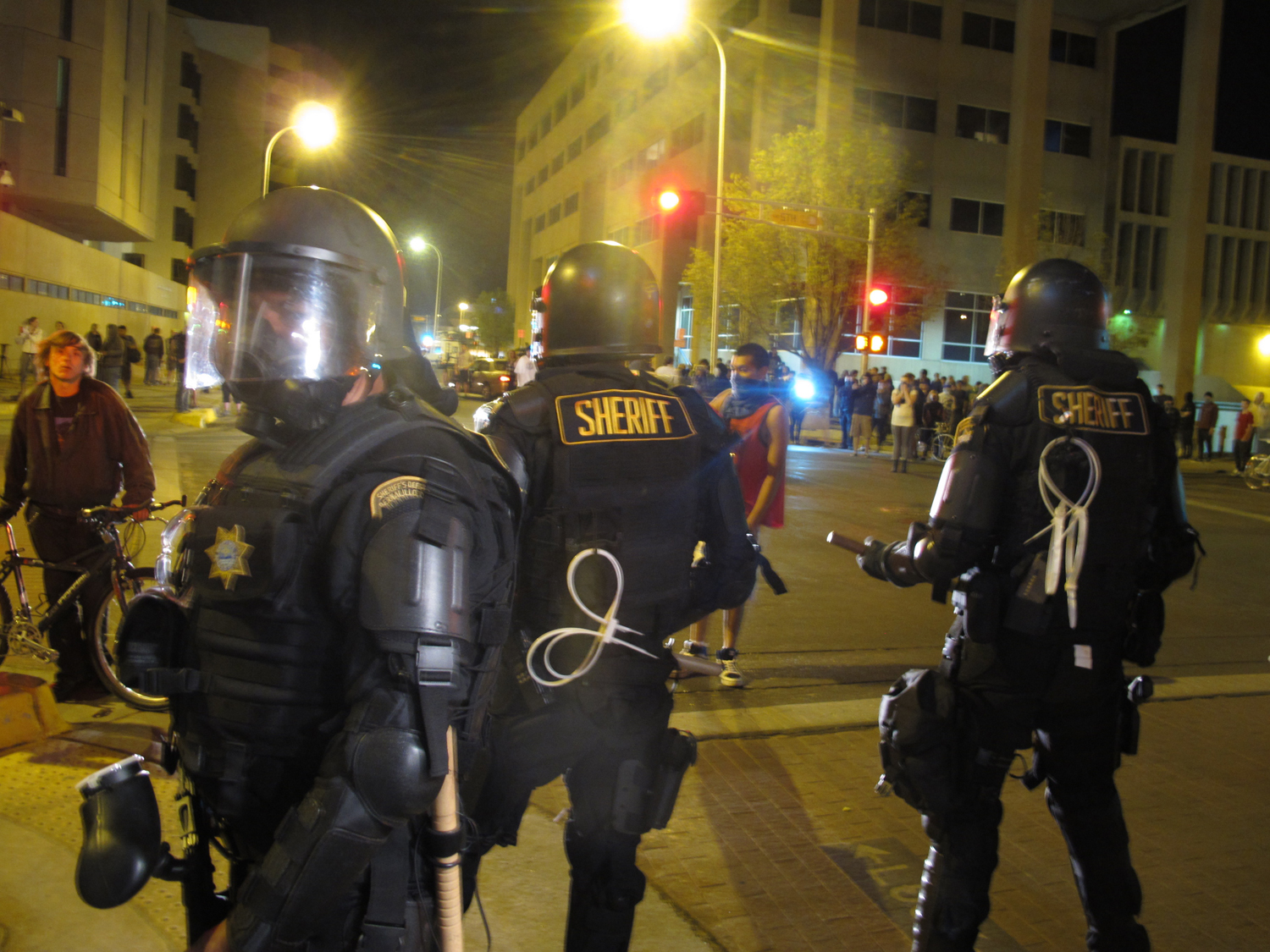 Riot police stand guard in front of protesters in downtown Albuquerque, N.M., Sunday, March 30,2014.