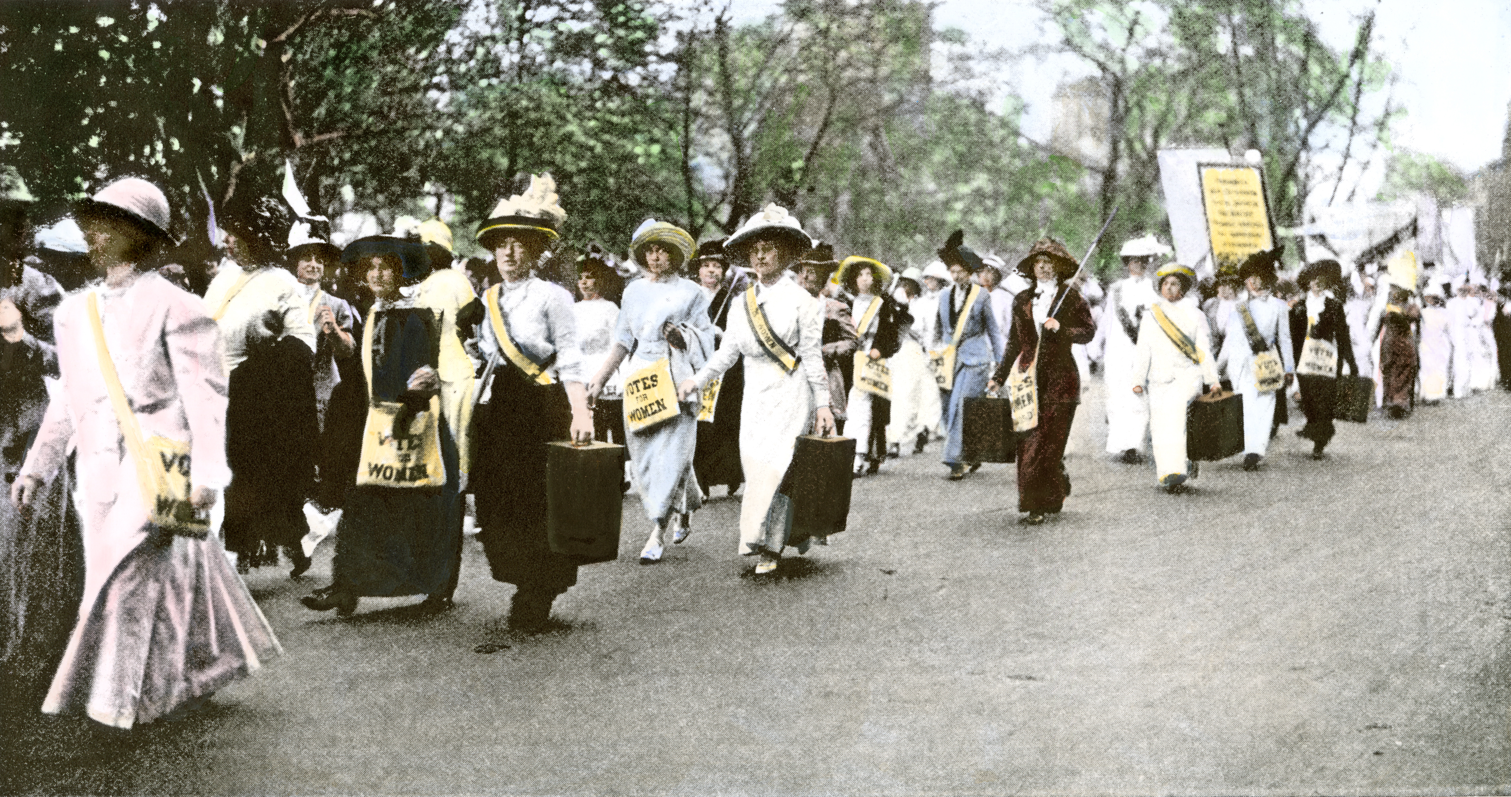 Suffragette marchers carrying portable speaker rostrums, New York City, 1912.                   Hand-colored halftone reproduction of a photograph