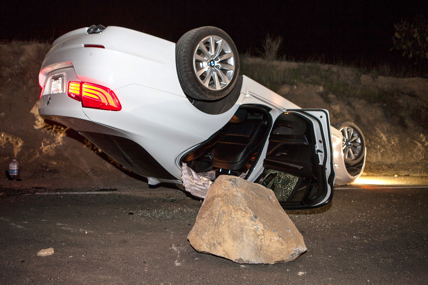 A car sits overturned on a highway in the Carbon Canyon area of Brea, Calif., March 28, 2014, after hitting a rock slide caused by an earthquake.