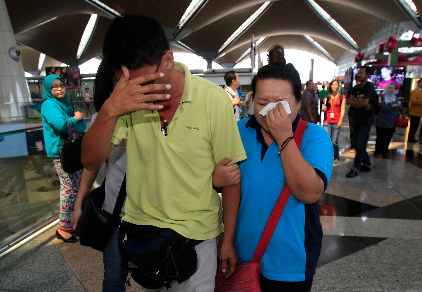 A woman wipes her tears after walking out from the reception center and holding area for family and friends of passengers aboard the missing plane, at Kuala Lumpur International Airport in Sepang, outside Kuala Lumpur, Malaysia, March 8, 2014.
