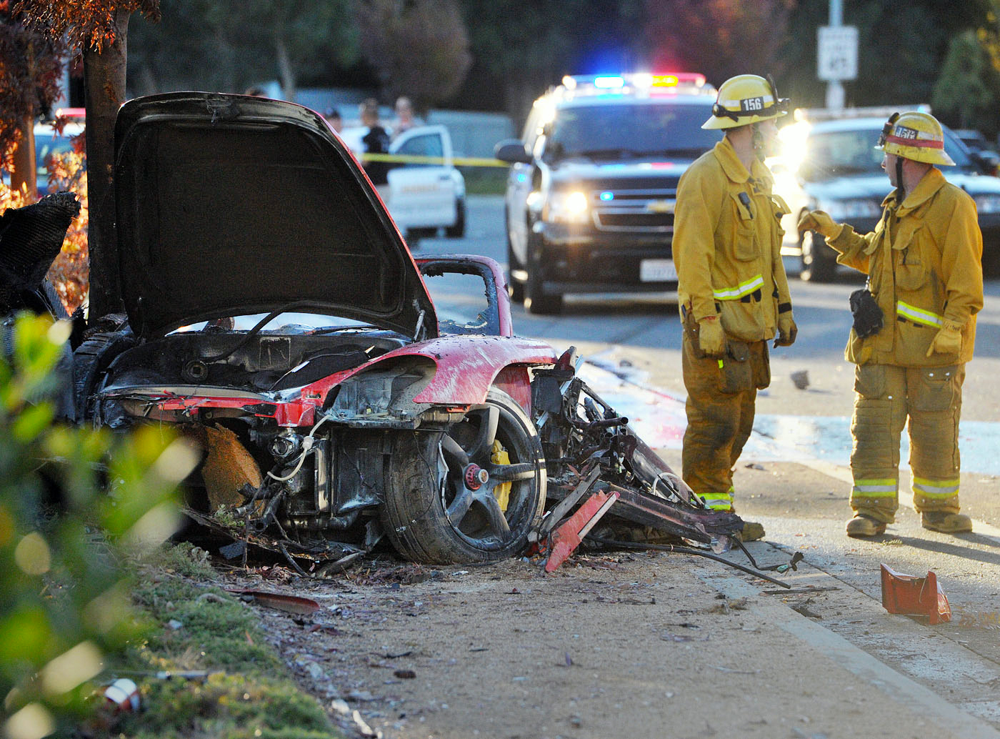 Firefighters work on Nov. 30, 2013 next to the wreckage of a Porsche that crashed into a light pole killing actor Paul Walker and Roger Rodas in Valencia, Ca.