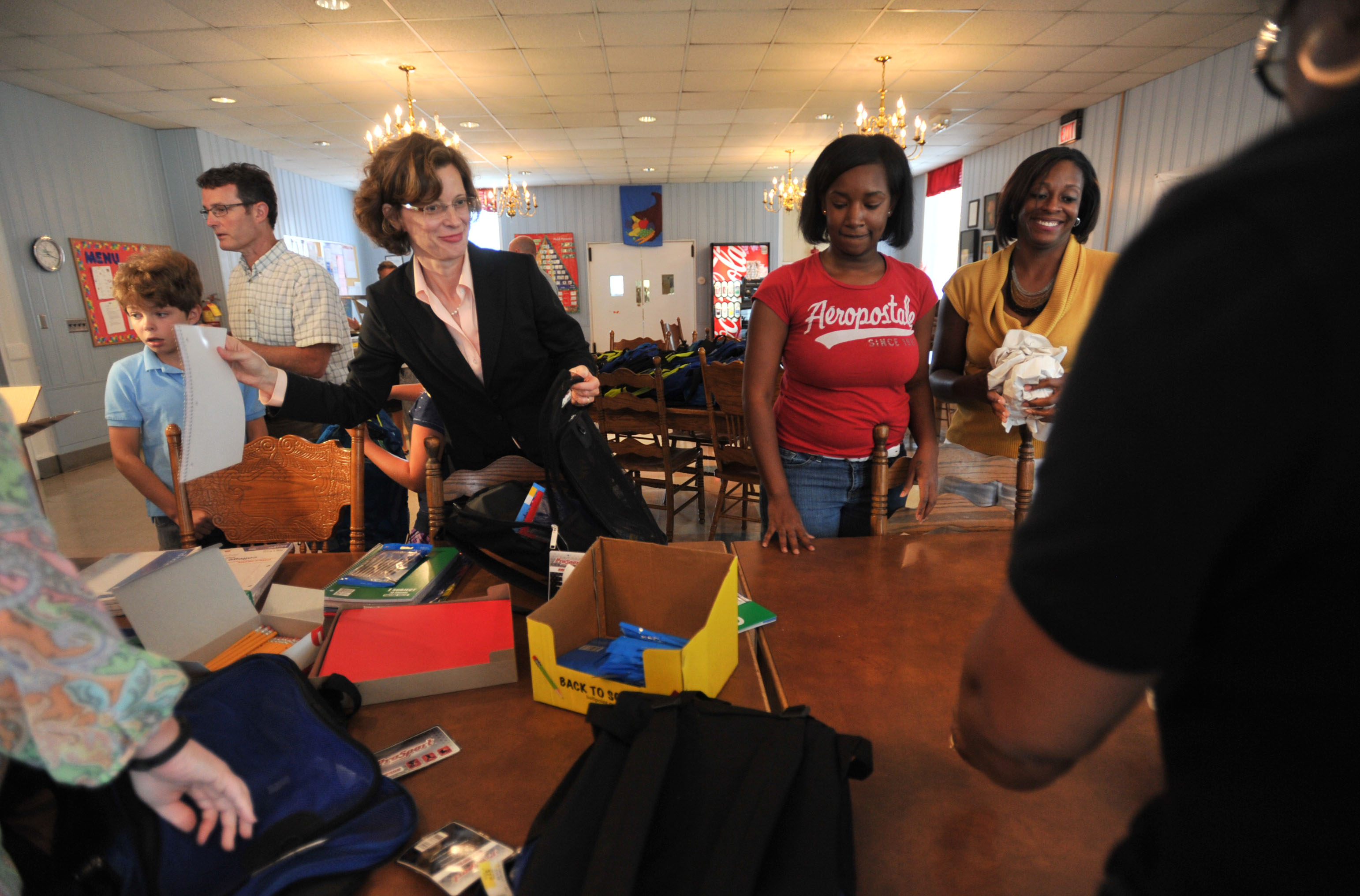 With the help of son, Vinson, left, and husband Ron, U. S. Senate candidate Michelle Nunn and other volunteers stuffed book bags with school supplies for residents of the Georgia Industrial Childrens Home, Aug. 7, 2013.