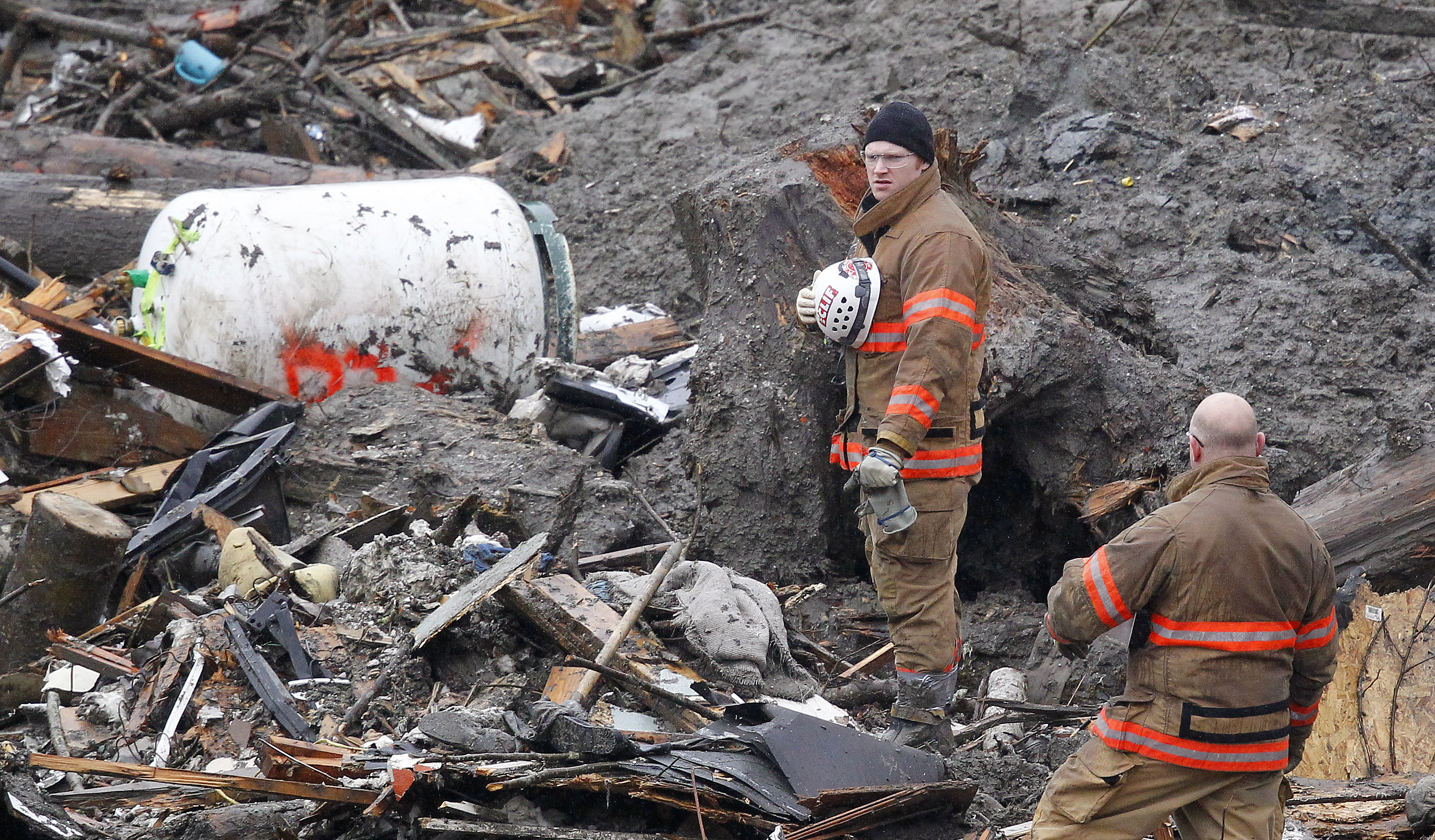 Searchers pause for a moment of silence at the scene of a deadly mudslide Saturday, March 29, 2014, in Oso, Wa.