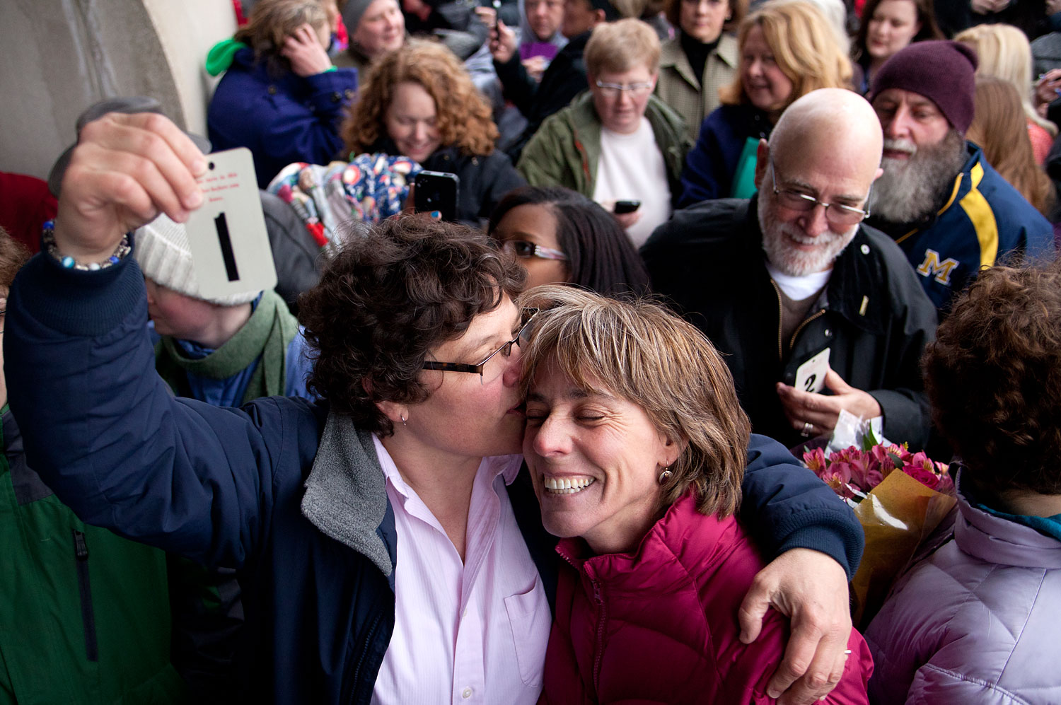 Elizabeth Patten, left, holds up the first marriage ticket to marry her partner Johnnie Terry in front of the Washtenaw County Clerks office in Ann Arbor, Mich., March 22, 2014, prior to the postponement of same-sex marriages by a federal appeals court.