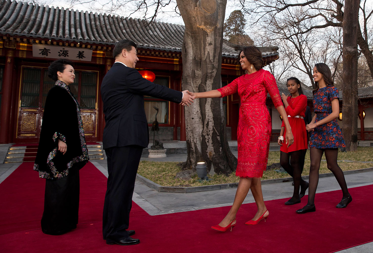 Obama, in a stunning red dress and matching shoes, greets Chinese President Xi Jinping and his wife Peng Liyuan at the Diaoyutai State guest house in Beijing, March 21, 2014.