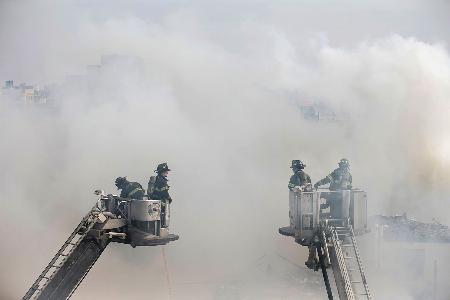 Firefighters respond to an explosion that leveled two apartment buildings in the East Harlem neighborhood of New York, March 12, 2014.