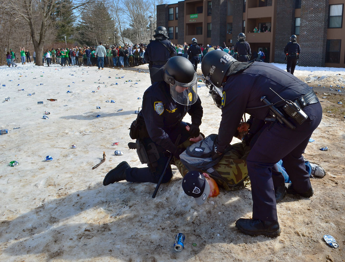 Police detain a participant in the pre-St. Patrick's Day  Blarney Blowout  near the University of Massachusetts in Amherst, Mass. March 8, 2014.