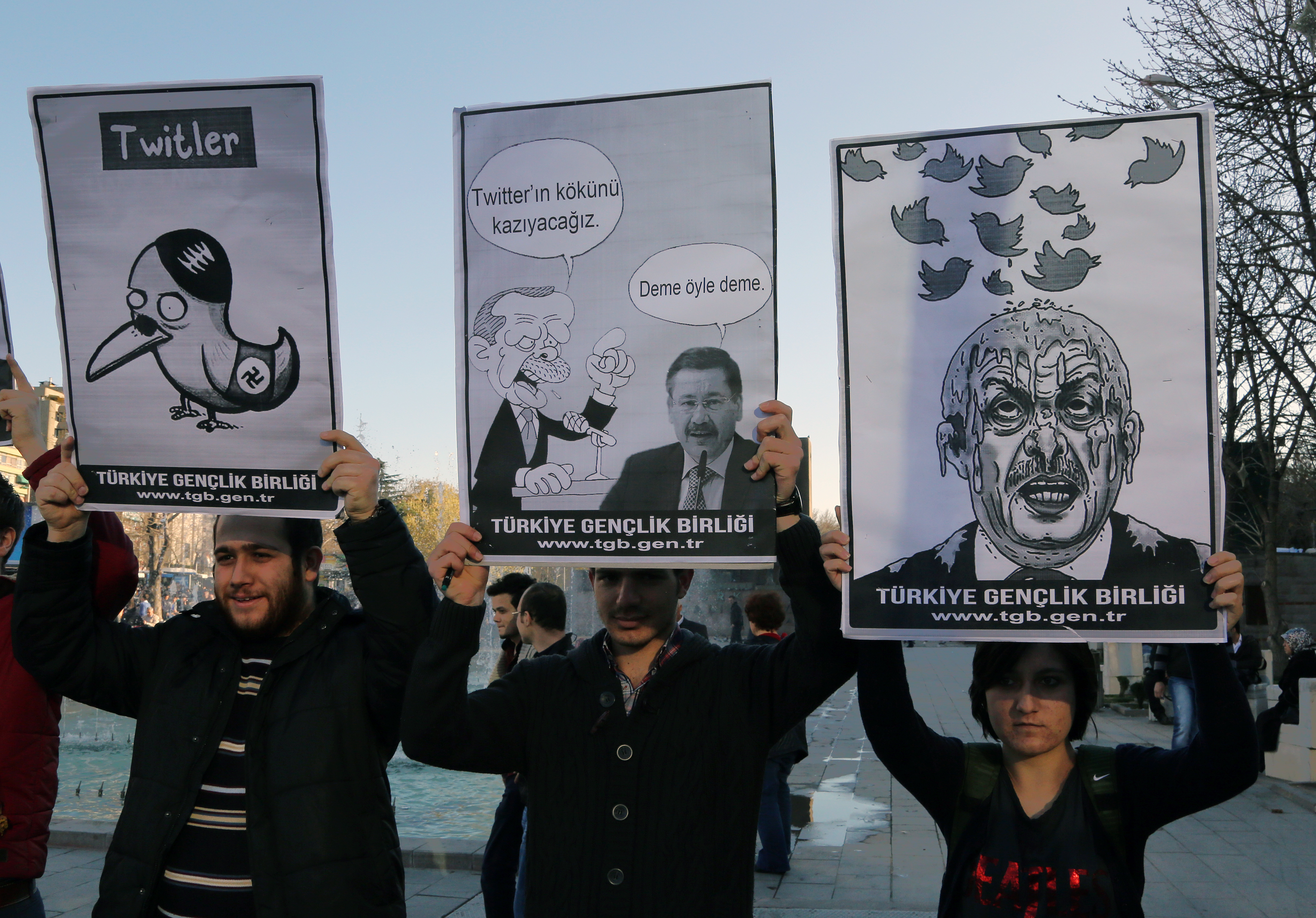 Members of the Turkish Youth Union hold cartoons depicting Turkey's Prime Minister Recep Tayyip Erdogan during a protest against a ban on Twitter on March 21, 2014, in Ankara