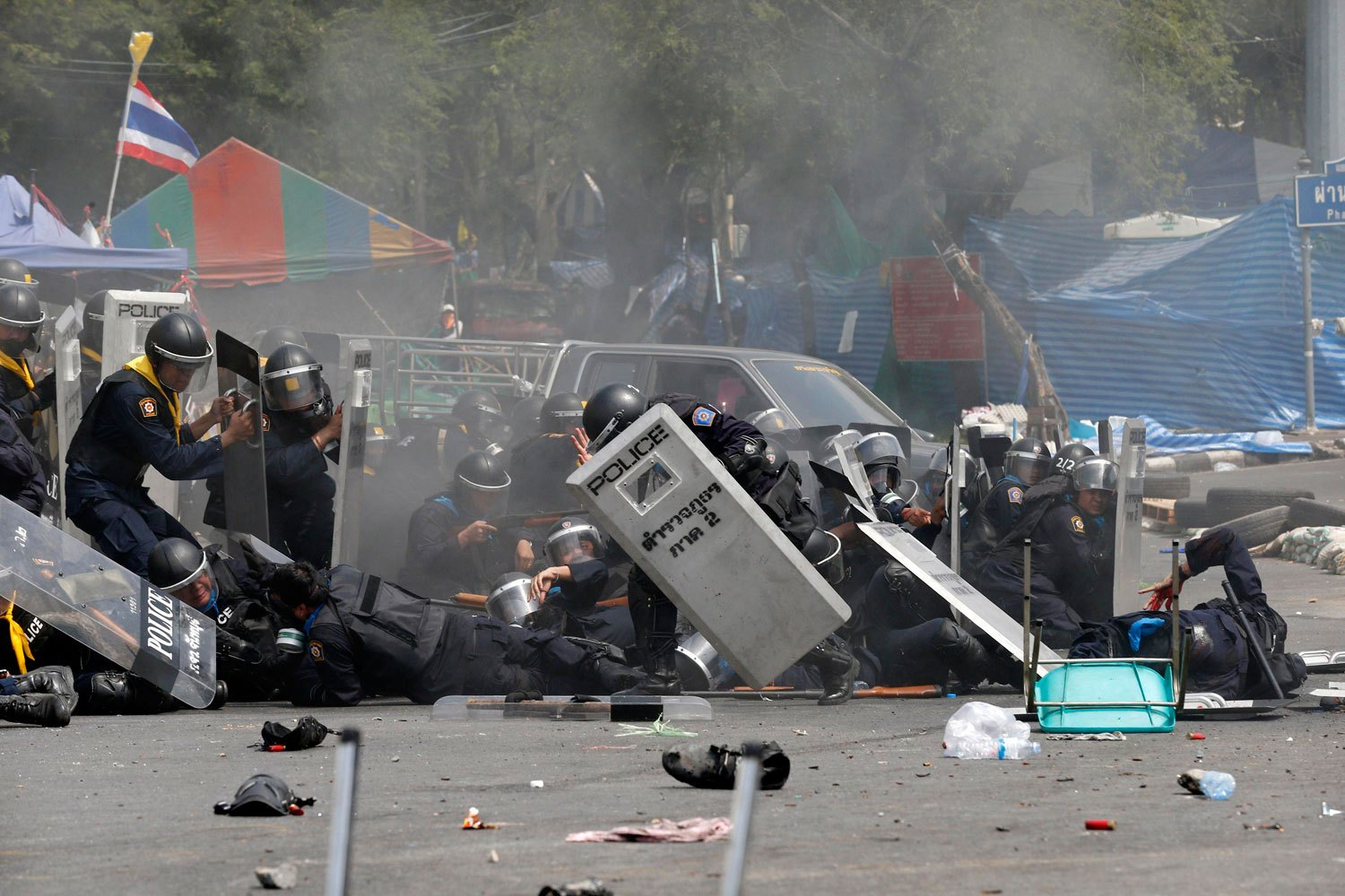 Thai police officers react after an explosion during clashes with anti-government protesters near Government House in Bangkok, on Feb. 18, 2014.