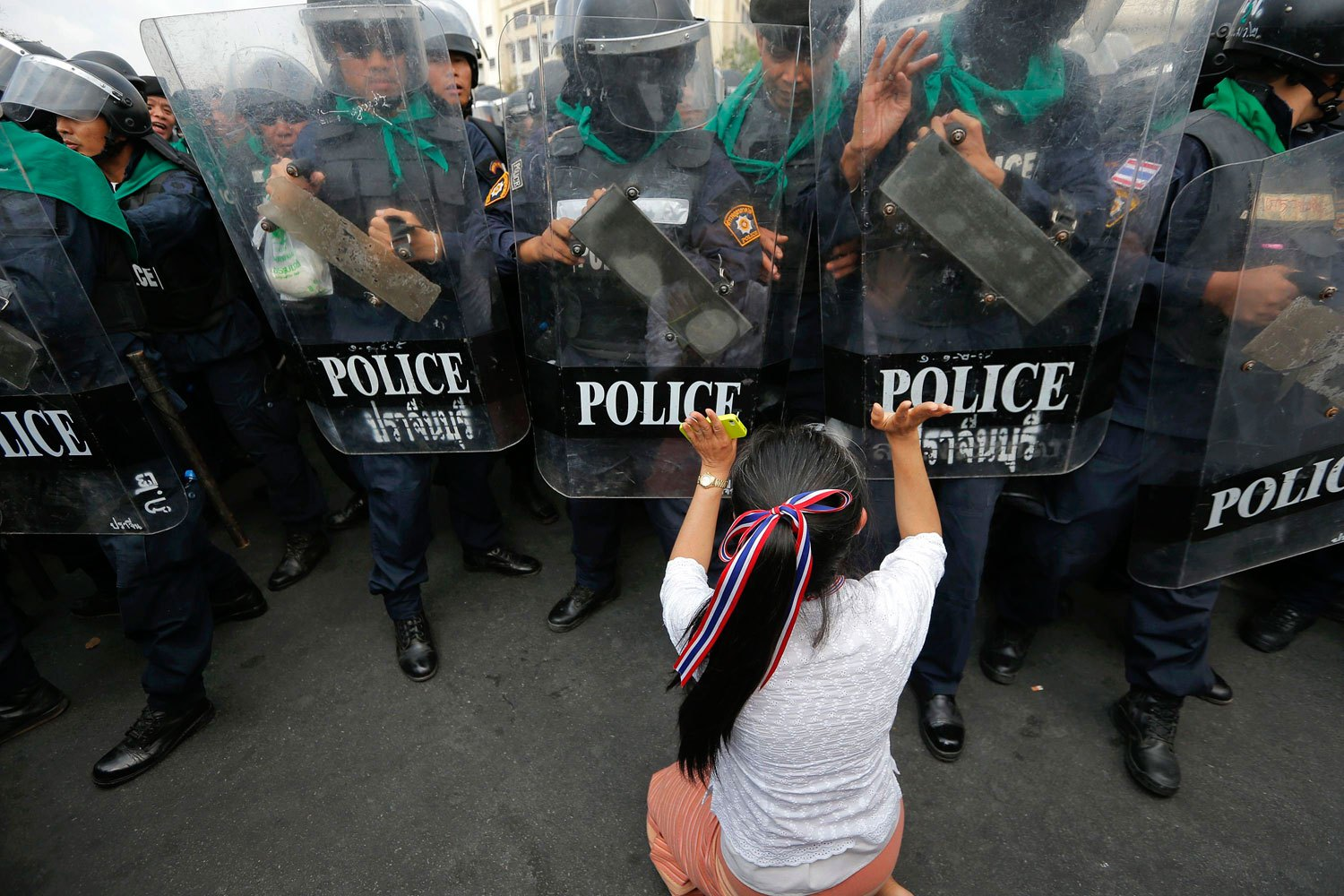 An anti-government protester pushes a line of policemen during clashes near the Government House in Bangkok, on Febr. 18, 2014.