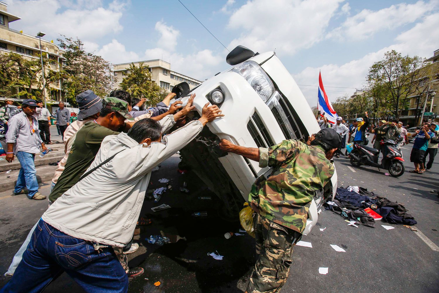 Anti-government protesters lift a police car after clashes with Thai riot police officers near Government House in Bangkok, on Feb. 18, 2014.