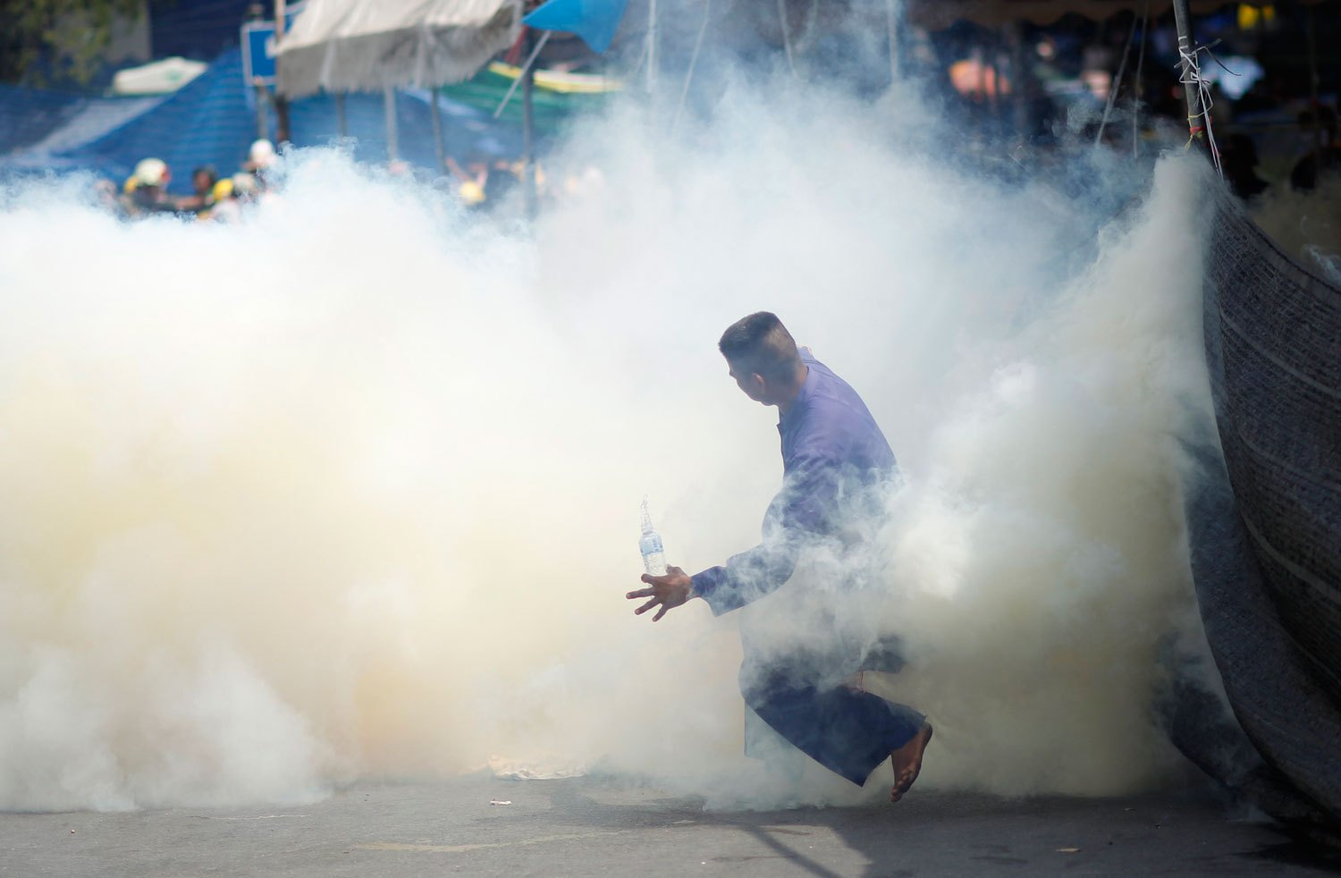 An anti-government protester is caught in tear gas during clashes with riot police in Bangkok, on Feb. 18, 2014.