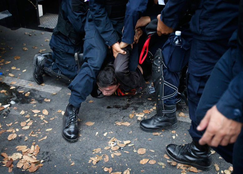 Thai police officers detain an anti-government protester near Government House in Bangkok, on Feb. 18, 2014.