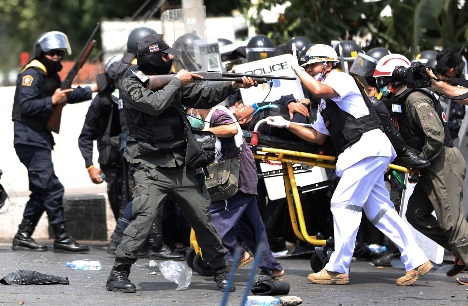 An armed Thai police officer aims his rubber bullet rifle as medical team carry a injured person on a stretcher during a clash between police force and anti-government protesters in Bangkok, on Feb. 18, 2014.