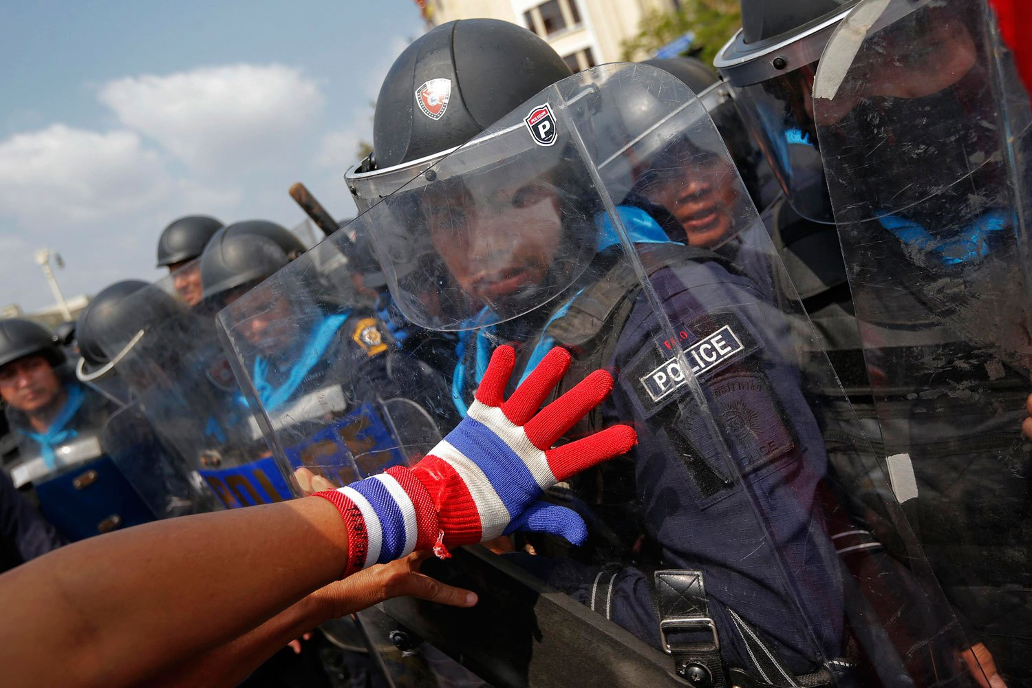 An anti-government protester pushes policemen during clashes near the Government House in Bangkok, on Feb. 18, 2014.