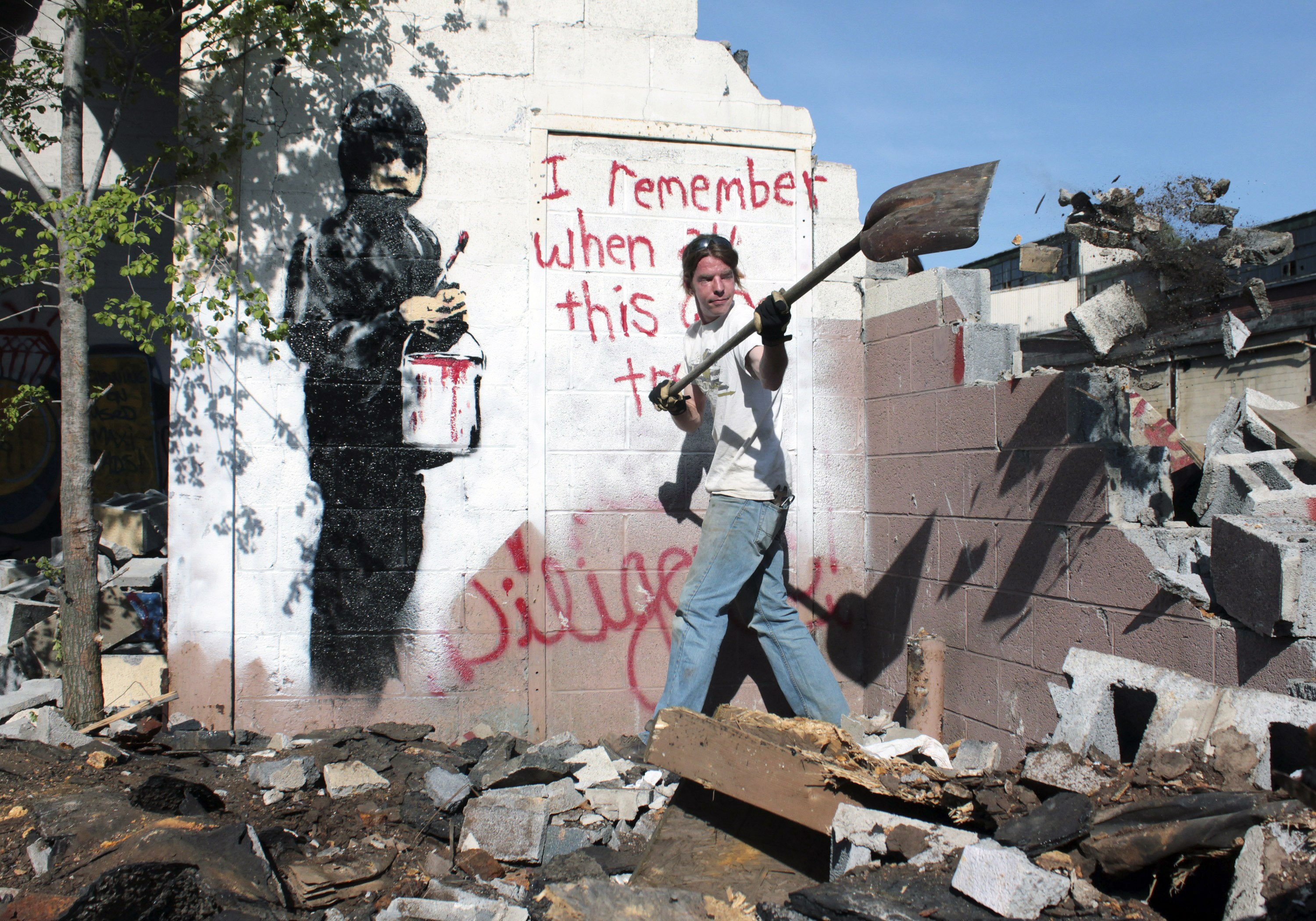 In this May 11, 2010 file photo Eric Froh,  conservator with 555 Nonprofit Gallery and Studios, clears the area around the stenciled artwork and message by British graffiti artist Banksy an abandoned car plant in Detroit before it was encased in a frame and taken to their gallery in Detroit.