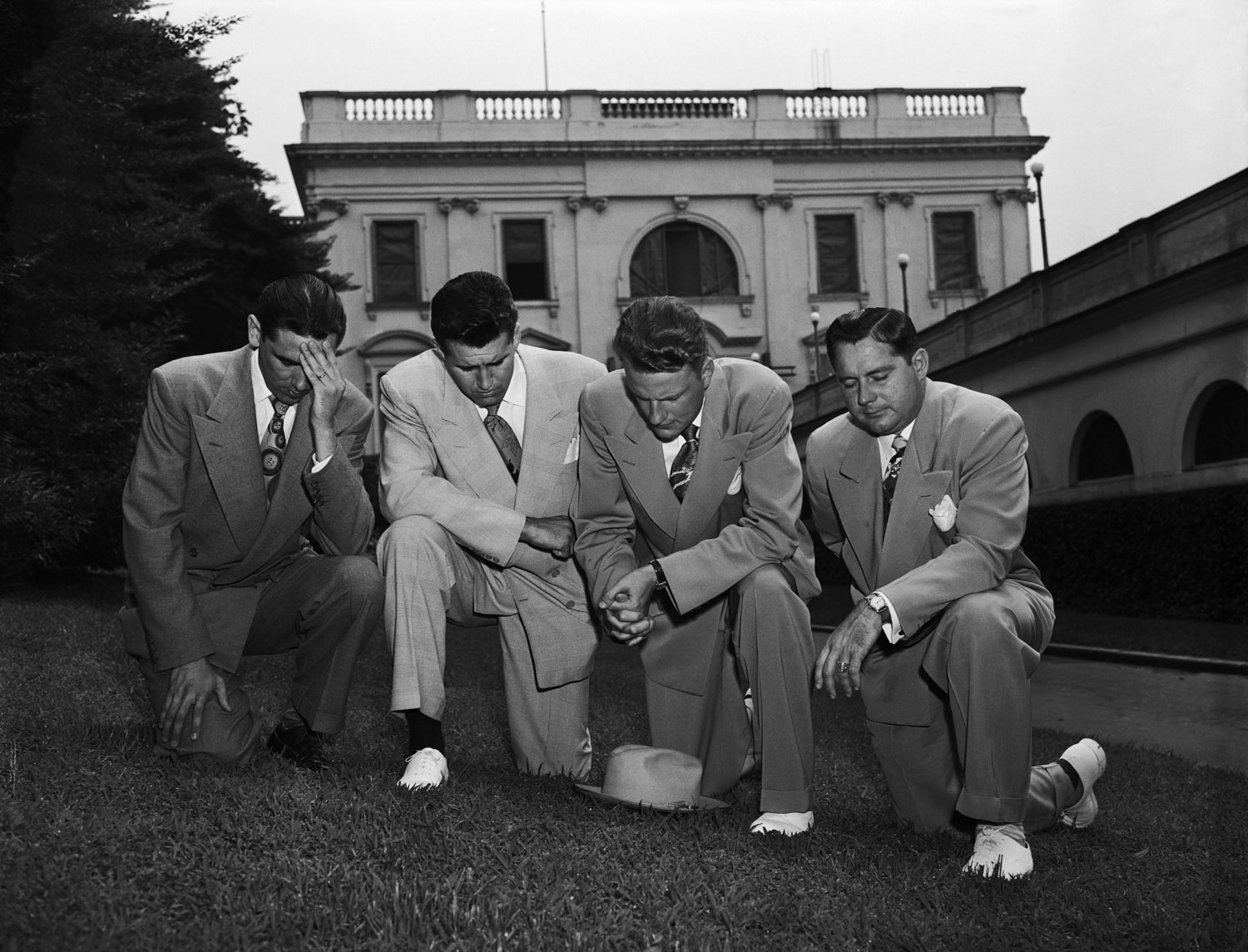 Foray into Washington                                                              Graham, behind hat, kneels in prayer with fellow evangelists, from left to right, Jerry Beavan, Cliff Barrows and Grady Wilson after meeting with President Harry Truman to discuss the Korean War, July 14, 1950.