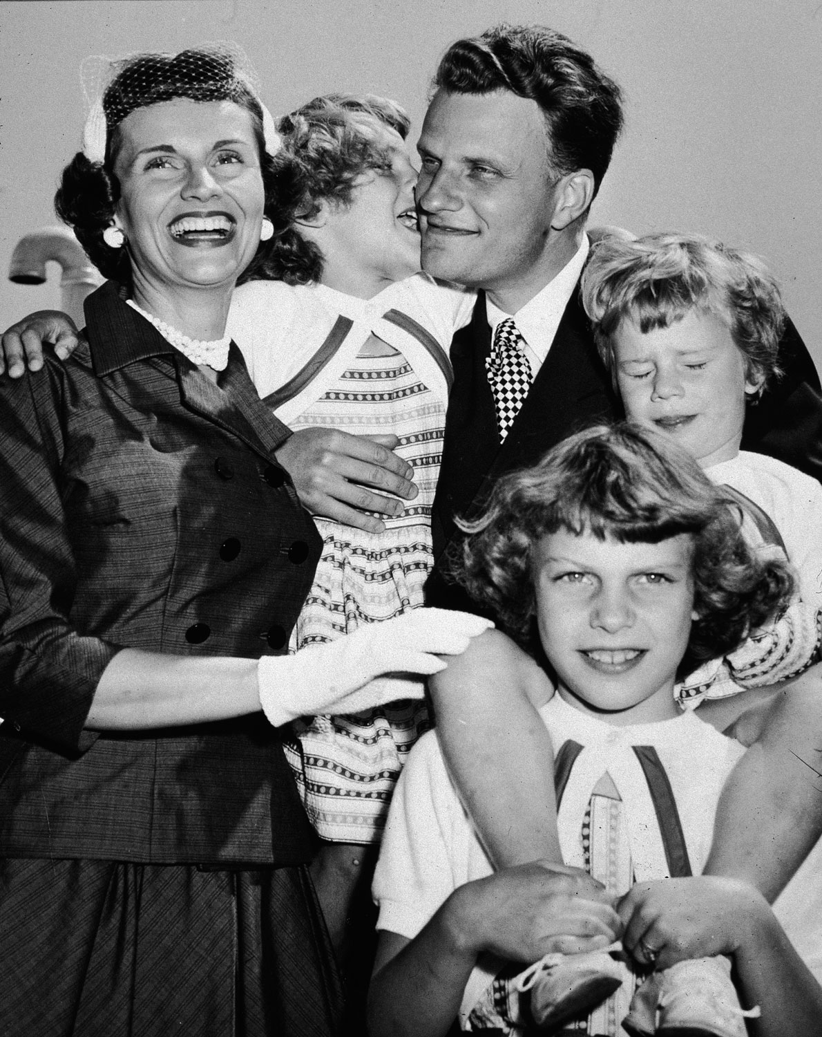 Family Values                                                              After returning from his 'Crusade for Christ' tour, Graham embraces his wife, Ruth, and his children in New York.
