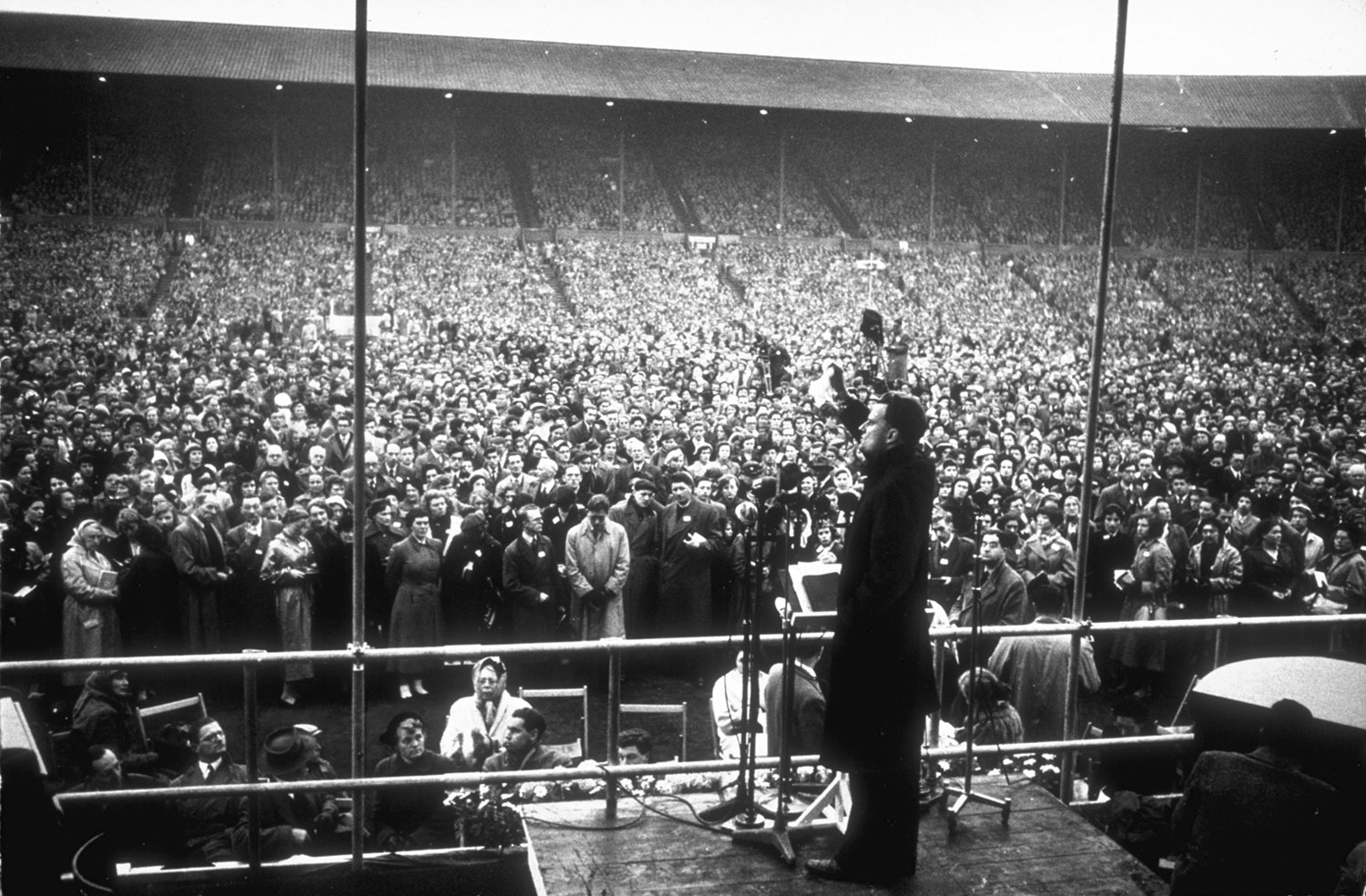 Graham waves a handkerchief while standing at a podium during a service in front of a crowd at Wembley Stadium.