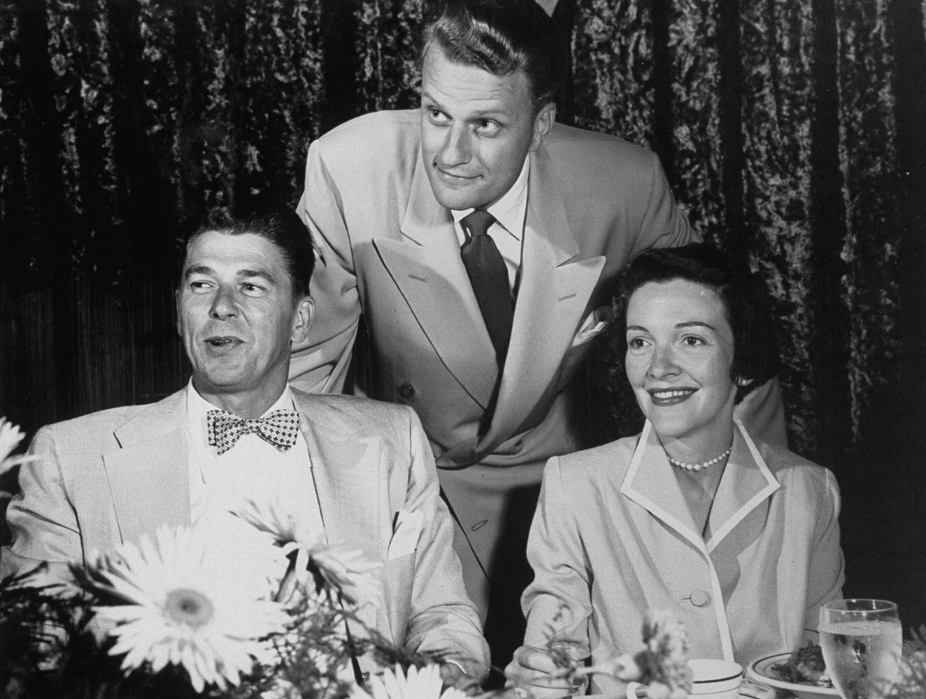 Long-Term Relationship                                                              Husband and wife actors Ronald Reagan and Nancy Davis mug with Graham at a movie exhibitors' meeting in Dallas, 1952. The friendship between Graham and Reagan lasted through his presidency.
