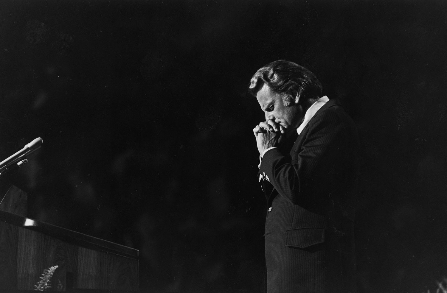 Touched                                                              Graham prays during a crusade in Charlotte, 1972.