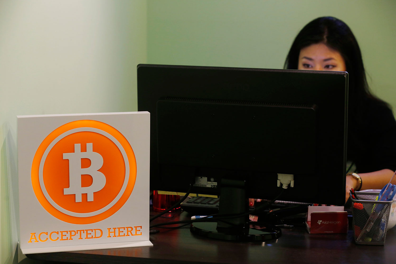 A staff member of ANXBTC Bitcoin Exchange works on the reception in Hong Kong, March 13, 2014.