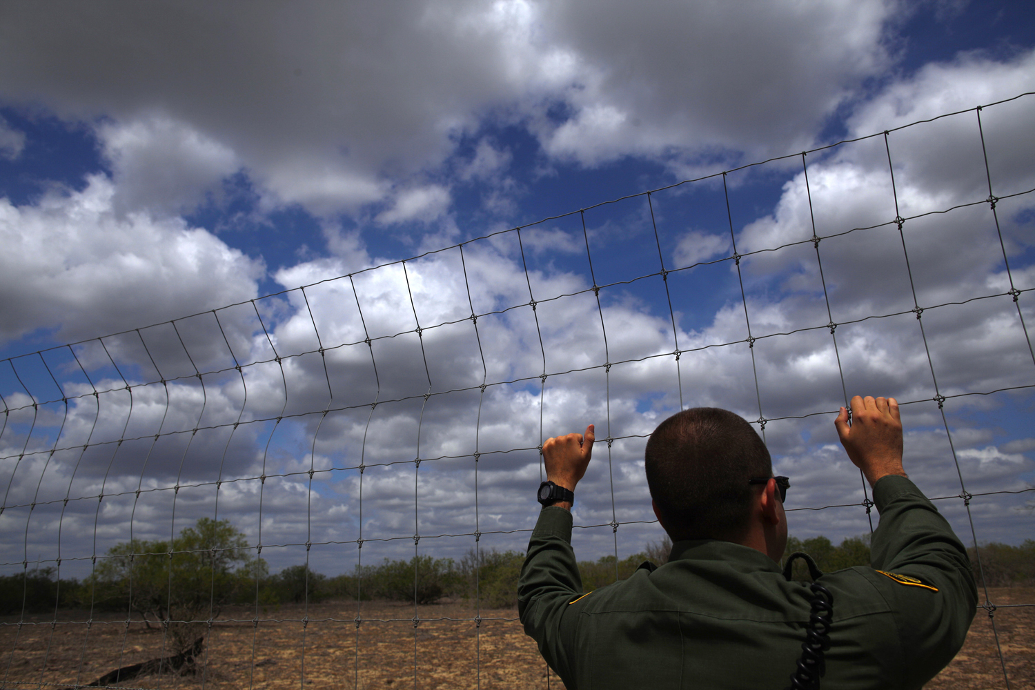 A U.S. Border Patrol agent looks out at the desert near Falfurrias, Texas March 29, 2013.