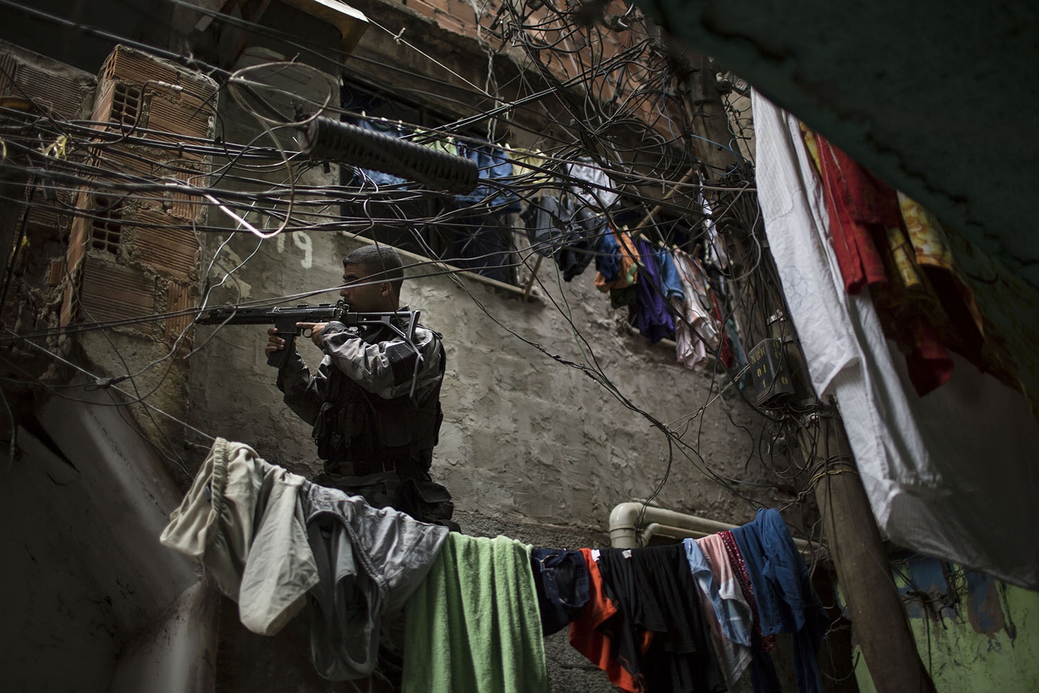 Mar. 25, 2014. Framed between makeshift clotheslines, a military police officer patrols during an operation in the Mare slum complex in Rio de Janeiro, Brazil.