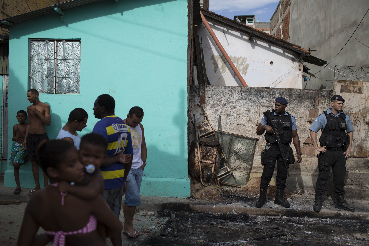 Mar. 21, 2014. Police officers stand guard among burned remains of a car from the Pacifying Police Unit post at the Mandela shantytown, part of the Manguinhos slum complex, in Rio de Janeiro, Brazil.