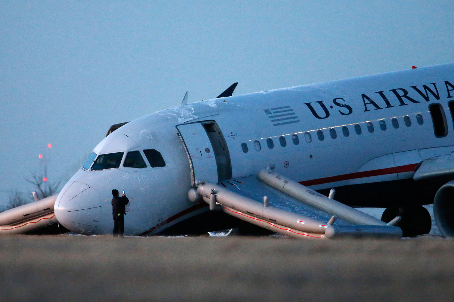 A person takes a photo of a damaged US Airways jet at the end of a runway at the Philadelphia International Airport, March 13, 2014, in Philadelphia.