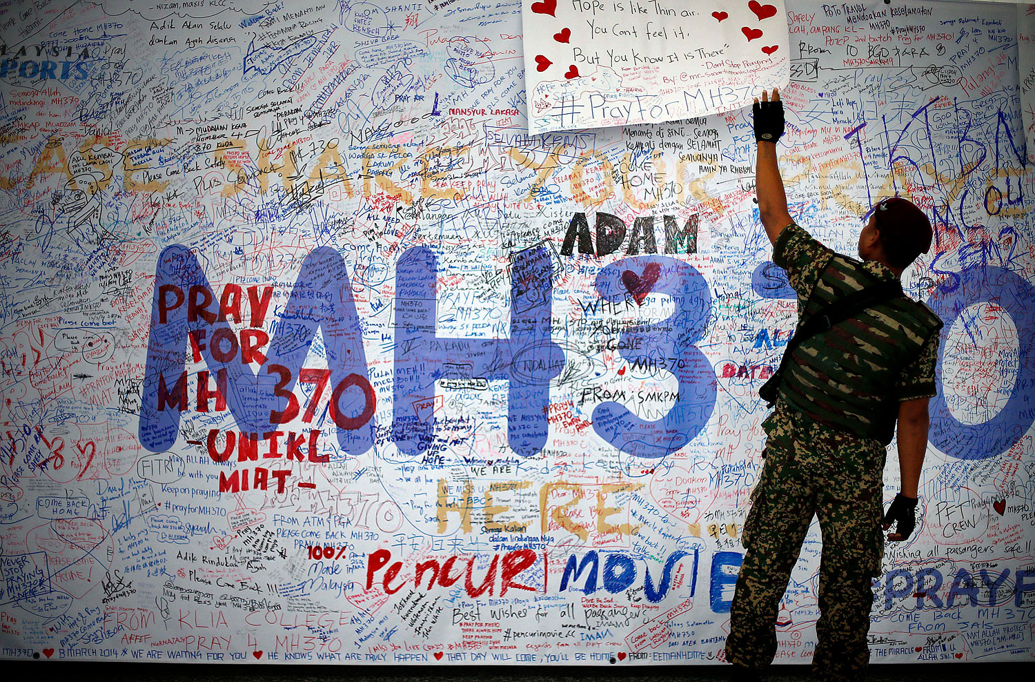 A Malaysian soldier patrols the viewing gallery of the Kuala Lumpur International Airport, where dedication boards with for people involved with the missing Malaysia Airlines jetliner is displayed, in Sepang, Malaysia, on March 16, 2014