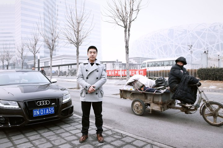 Zhao Xiadi next to his Audi A5 with National Stadium in the background. Beijing, China, Chaoyang District. February 15, 2014