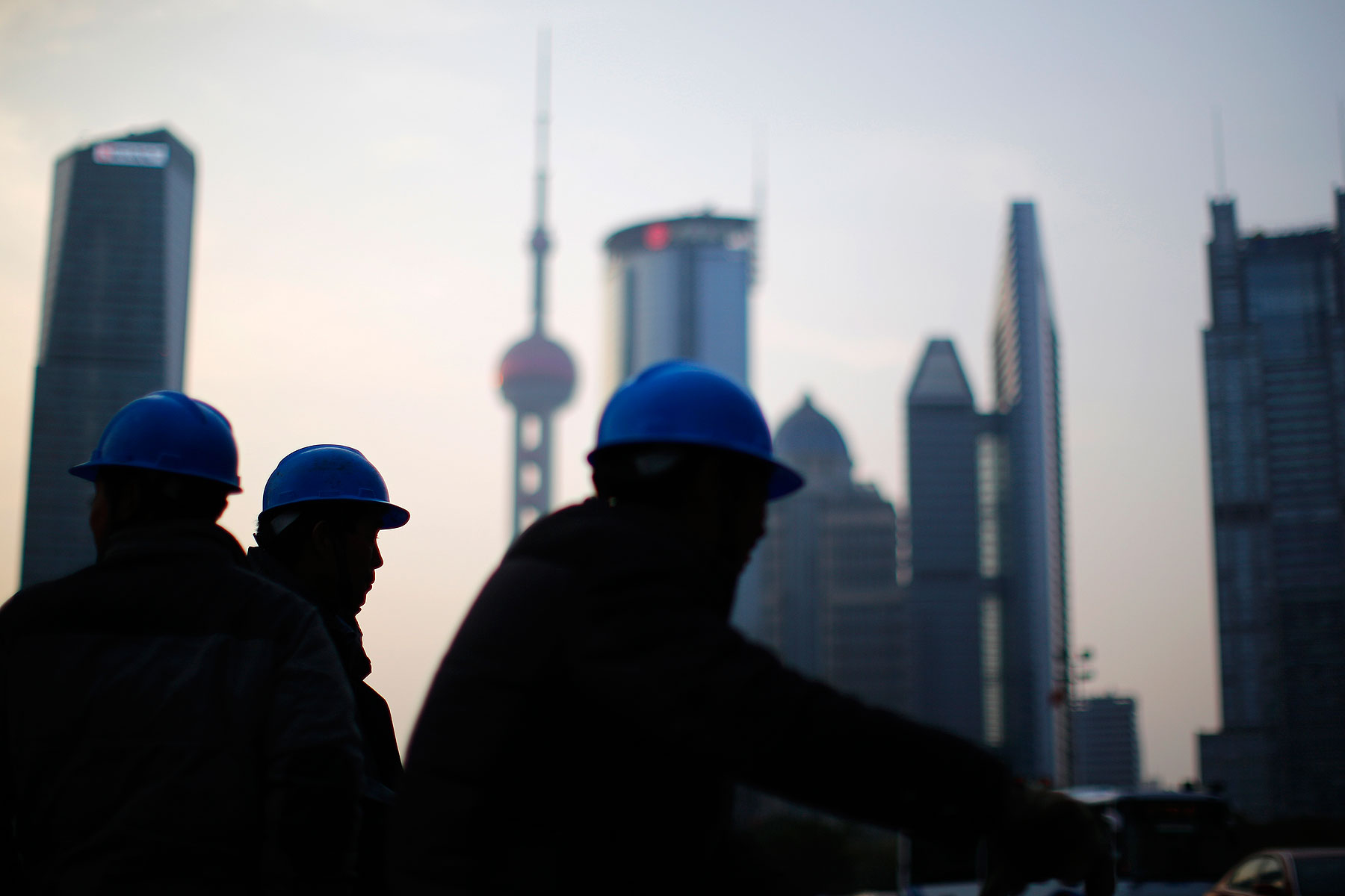 Construction workers stand on a street corner at the financial district of Pudong in Shanghai on March 11, 2014