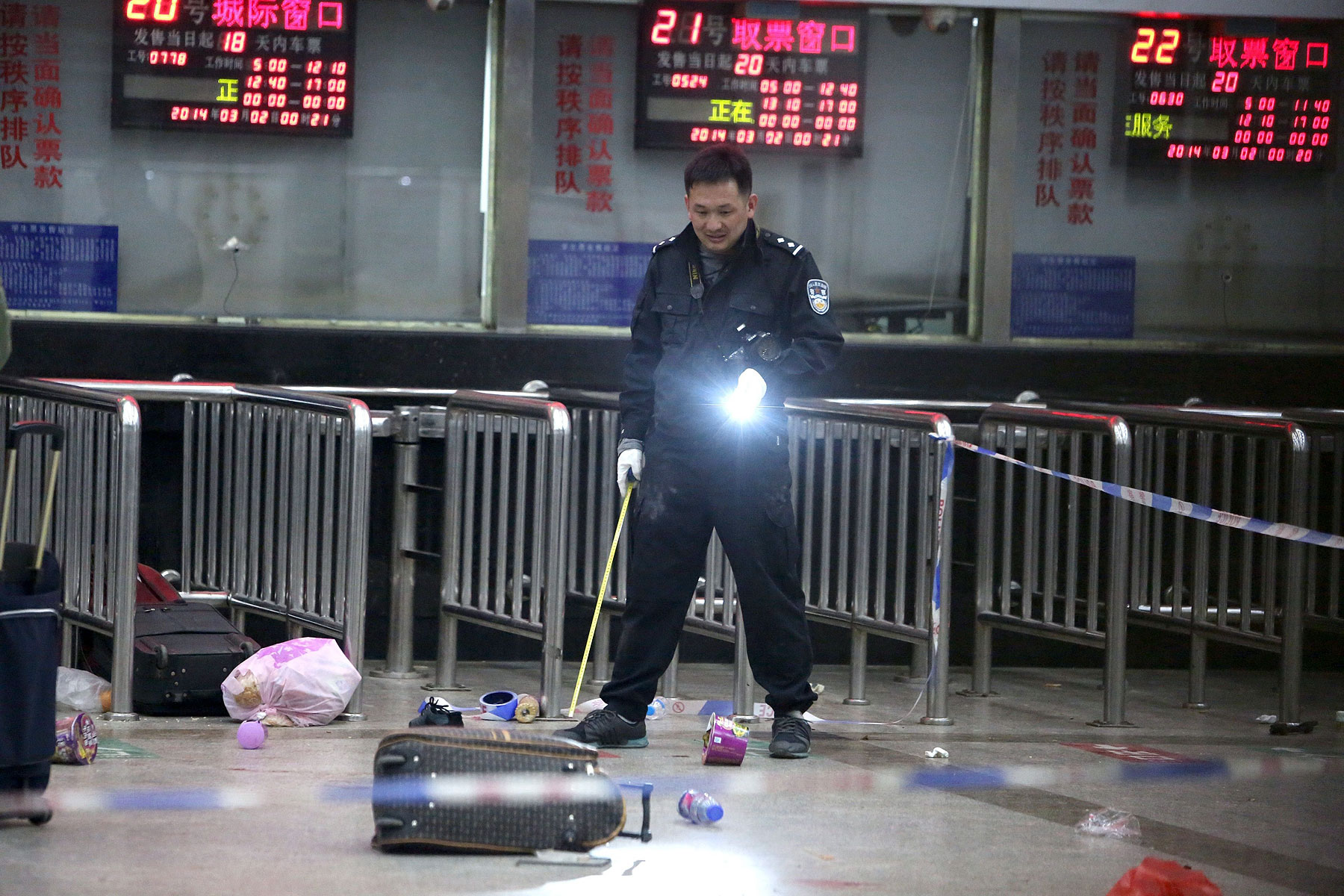 A Chinese police investigator in Kunming's railway station after the March 1 mass knifings that killed 29 people and injured scores