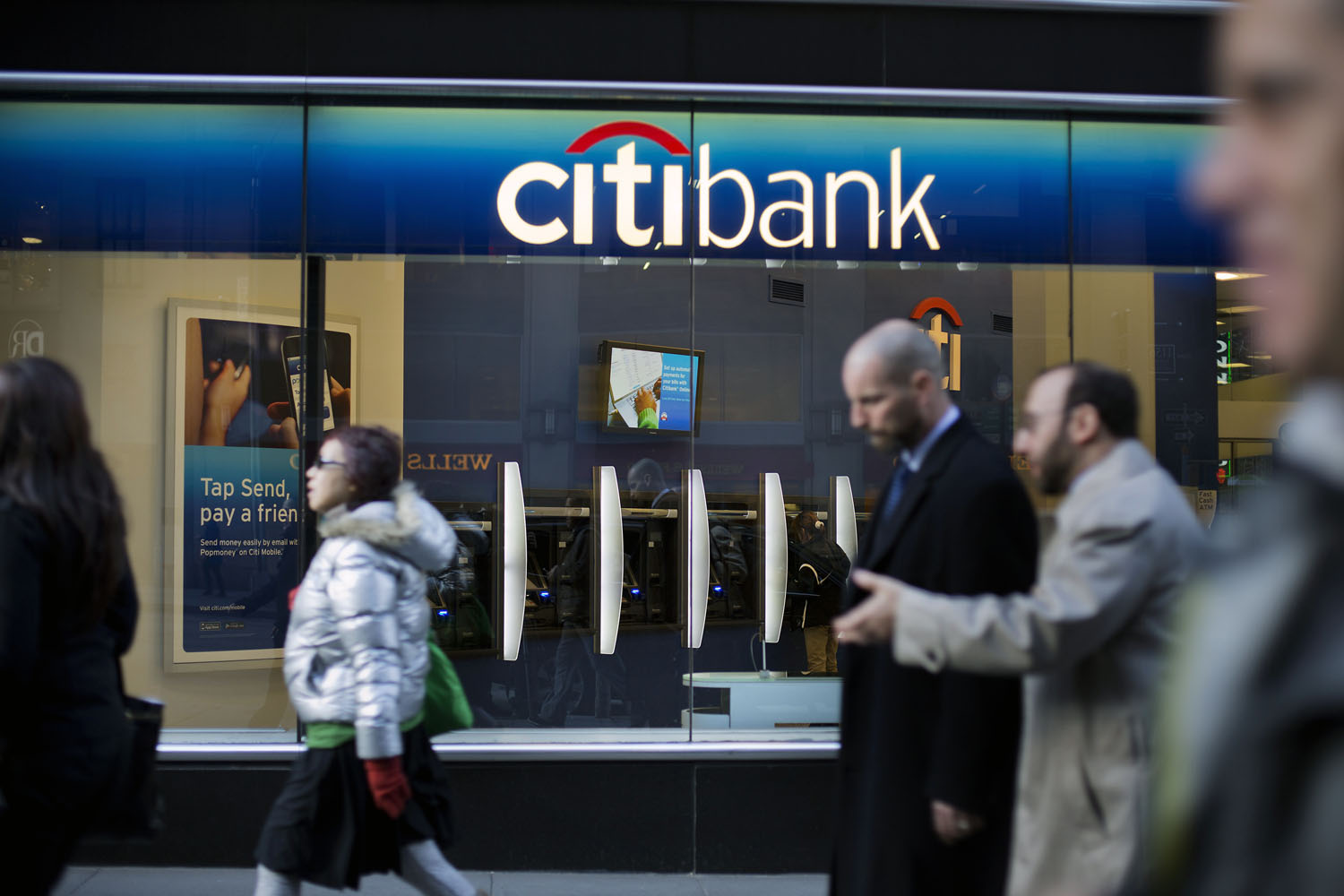 Pedestrians walk past a Citigroup Inc. Citibank branch in New York, U.S., on Tuesday, March 5, 2013. The six largest U.S. banks may return almost $41 billion to investors in the next 12 months, the most since 2007, as regulators conclude firms have amassed enough capital to withstand another economic shock. Photographer: Victor J. Blue/Bloomberg via Getty Images