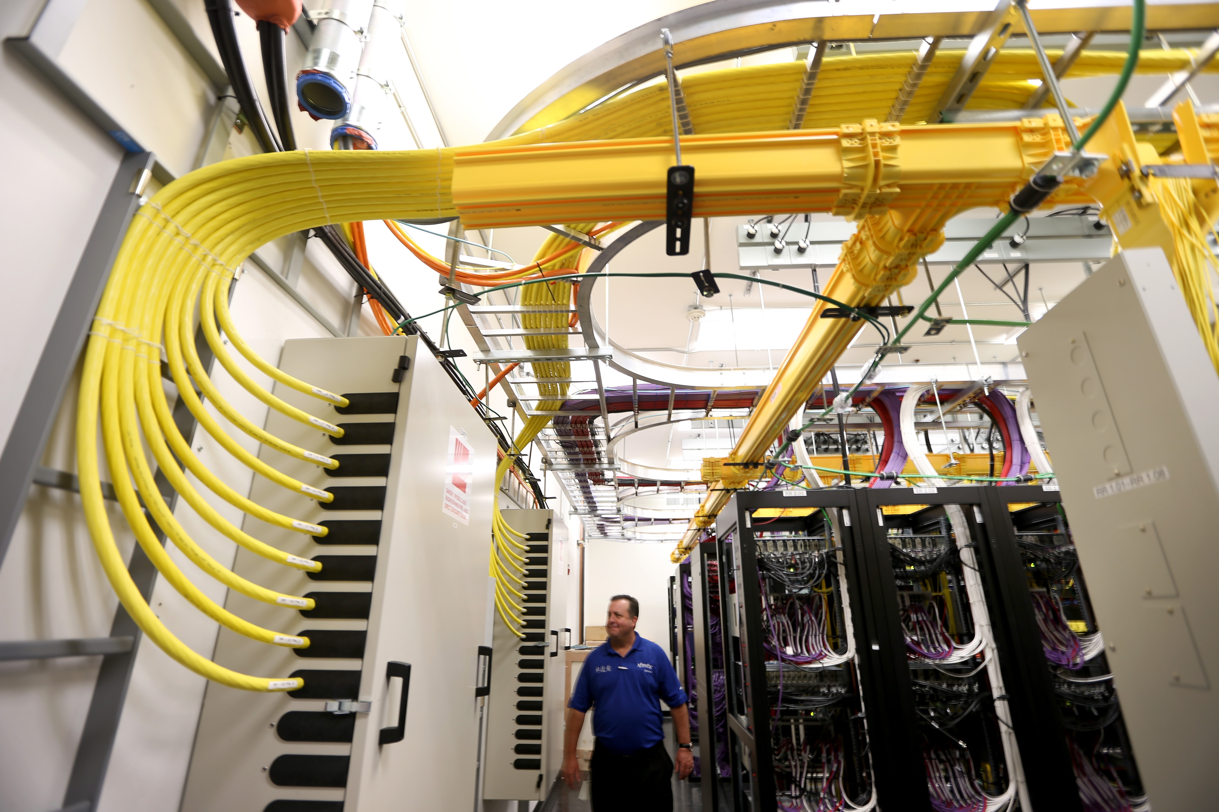 Brian Hunt,  Director Engineering, South Florida, stands among the cables and routers at a Comcast distribution center where the Comcast regional video, high speed data and voice are piped out to customers on February 13, 2014 in Miramar, Fla.