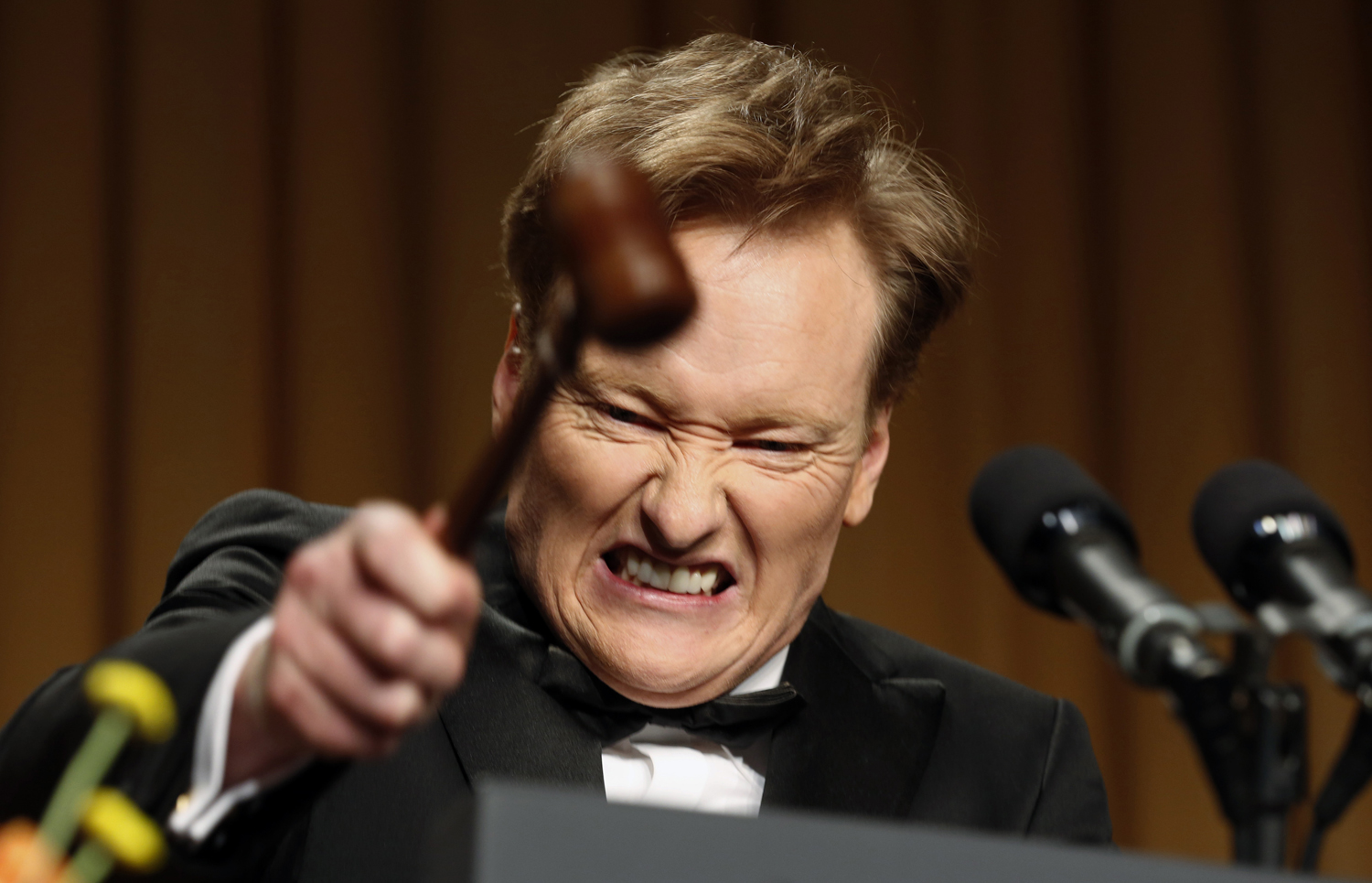 Comedian Conan O'Brien smashes a gavel as he speaks during the White House Correspondents Association Dinner in Washington April 27, 2013