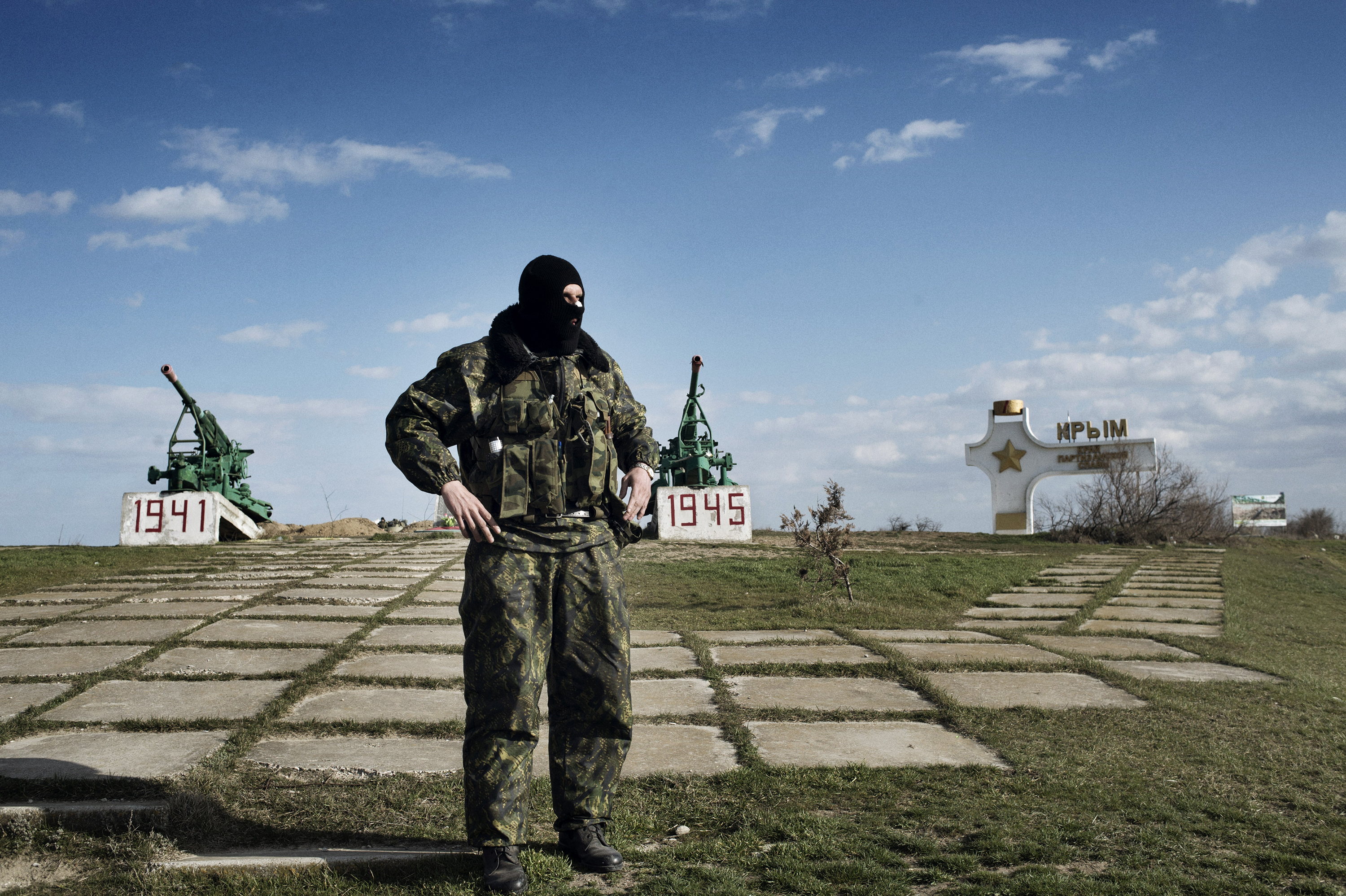 A pro-Russian militiaman stands at a war memorial near what is now the border between Crimea and Ukraine.