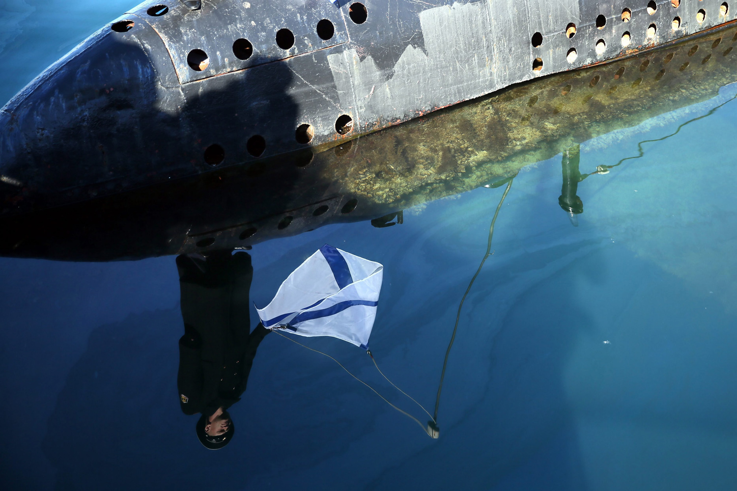 Mar. 22, 2014.  A Russian sailor holding the Russian Navy's St. Andrew flag while standing on the on bow of the surrendered Ukrainian submarine 'Zaporozhye', is reflected in the waters of the harbor of Sevastopol, Crimea, Ukraine.